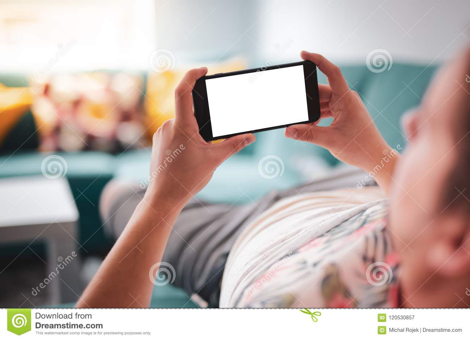 Άτομο που χρησιμοποιεί το smartphone οριζόντιο στον καναπέ