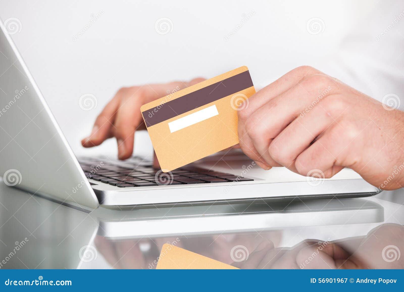 Άτομο που ψωνίζει με την πιστωτική κάρτα και το lap-top