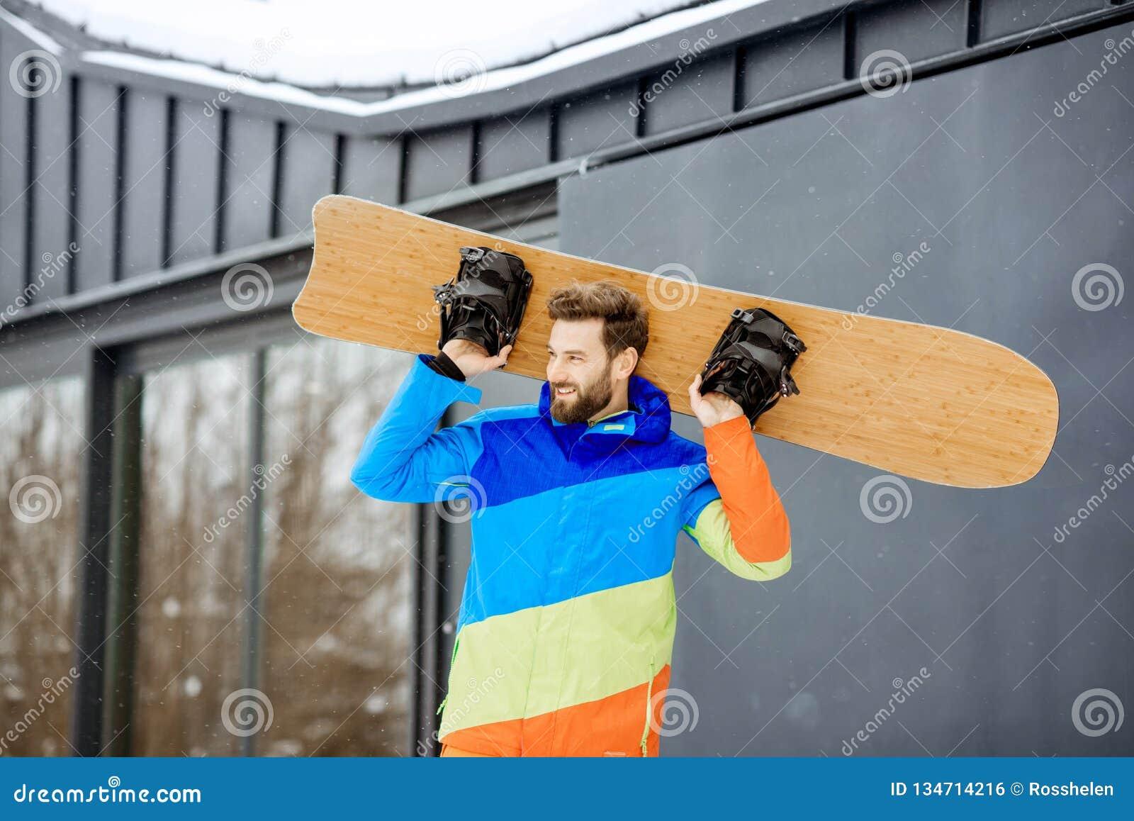 Άτομο στο κοστούμι σκι κοντά στο σπίτι στα βουνά
