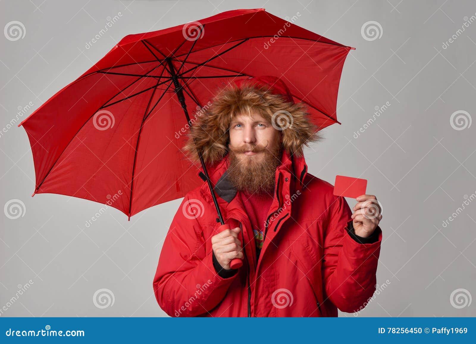 Άτομο στο χειμερινό σακάκι με την ομπρέλα που παρουσιάζει κενή πιστωτική κάρτα