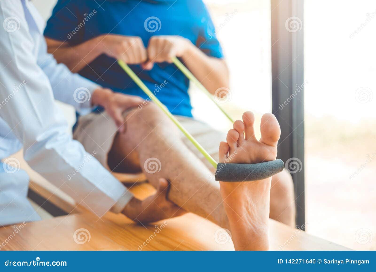 Άτομο φυσιοθεραπευτών που δίνει τη θεραπεία άσκησης ζωνών αντίστασης για το γόνατο της αρσενικής υπομονετικής φυσικής έννοιας θερ
