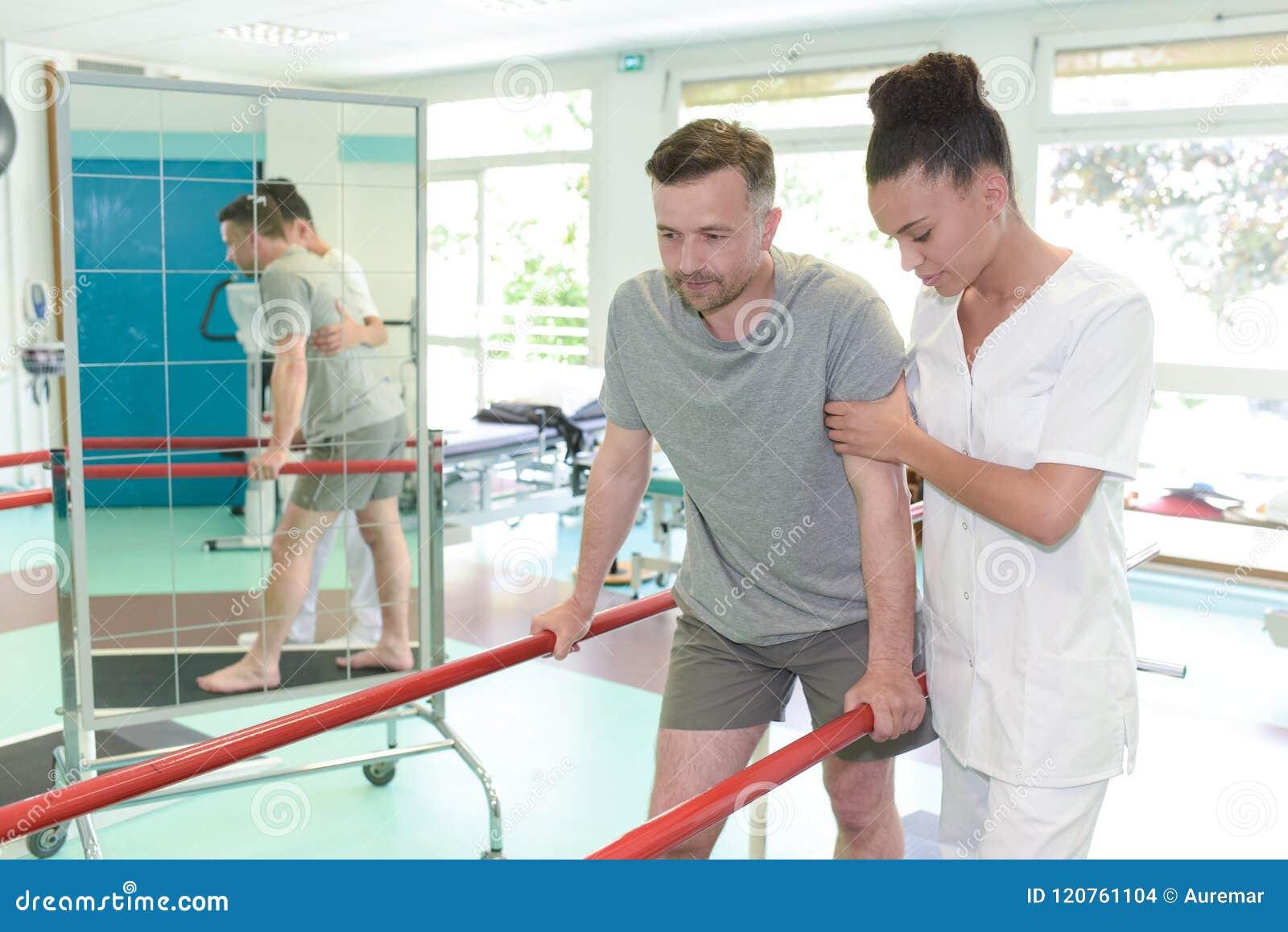 Άτομο treadmill με το σκύψιμο θεραπόντων στο στούντιο ικανότητας