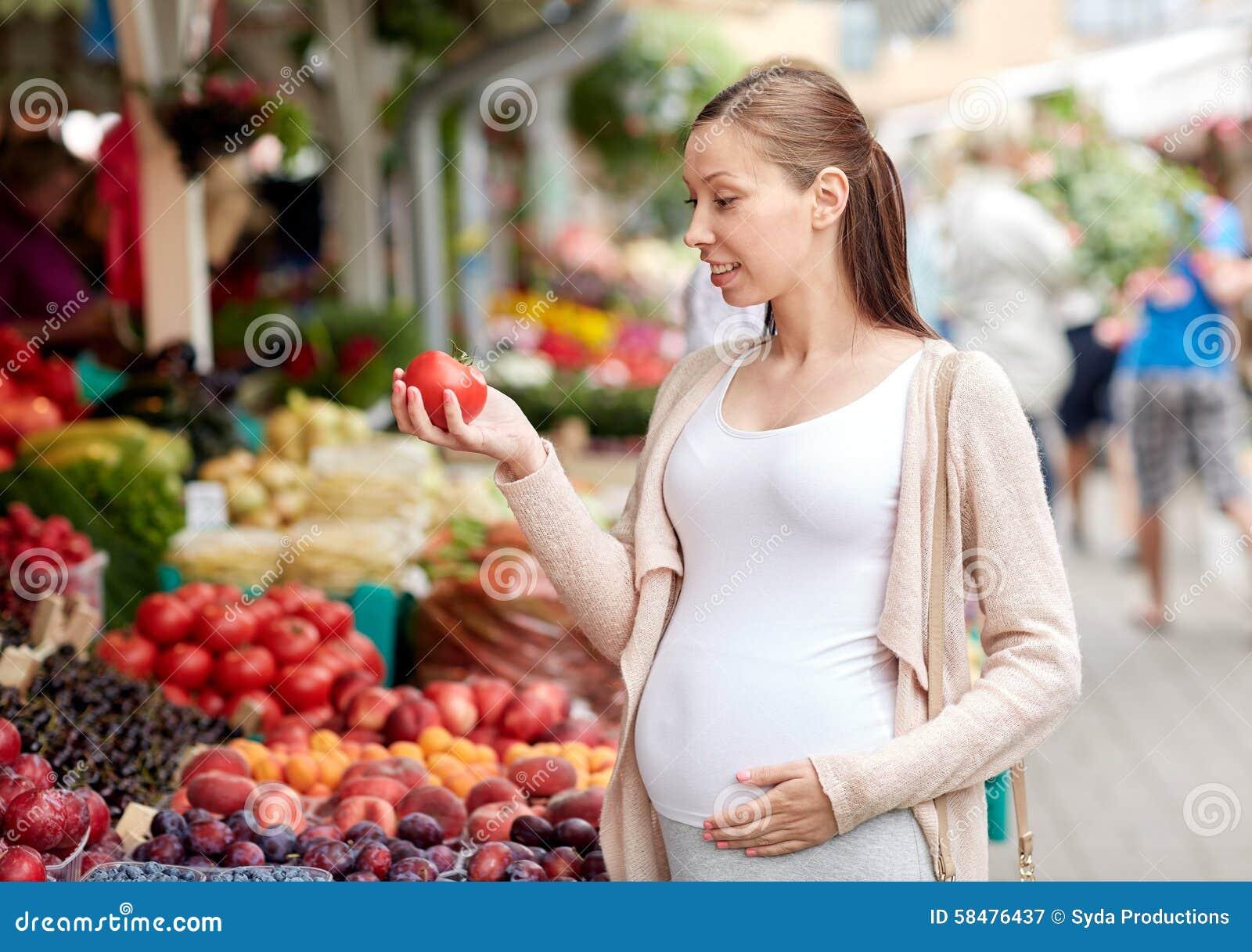 Έγκυος γυναίκα που επιλέγει τα τρόφιμα στην αγορά οδών