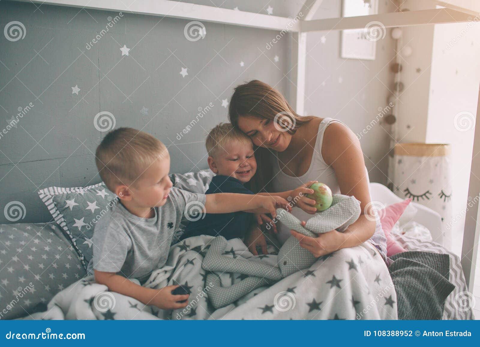 Έγκυος μητέρα και δύο γιοι διαβάζουν ένα ενδιαφέρον βιβλίο στο σπίτι το πρωί Περιστασιακός τρόπος ζωής στην κρεβατοκάμαρα