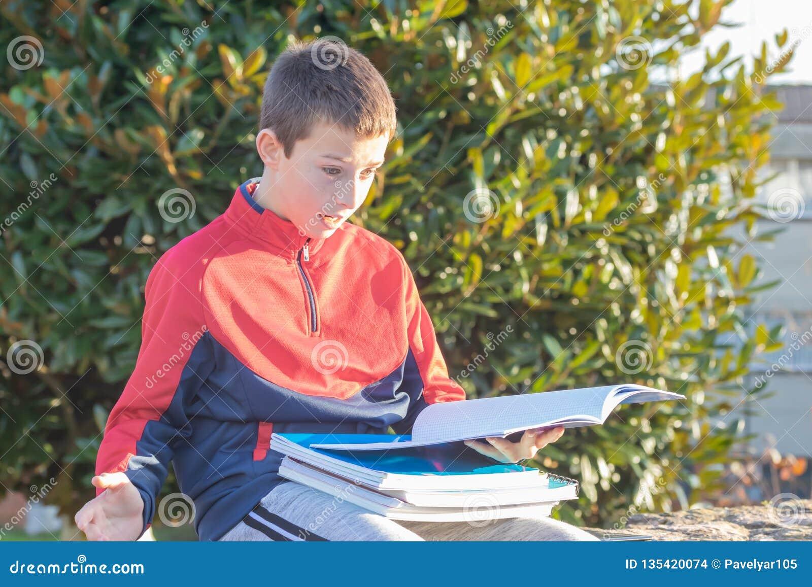 Έκπληκτος έφηβος με τα εγχειρίδια και τα σημειωματάρια
