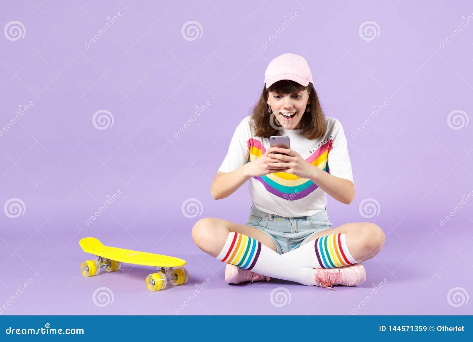 Έκπληκτο κορίτσι εφήβων στα ζωηρά ενδύματα που κάθεται κοντά skateboard που χρησιμοποιεί το κινητό μήνυμα τηλεφωνικής δακτυλογράφ
