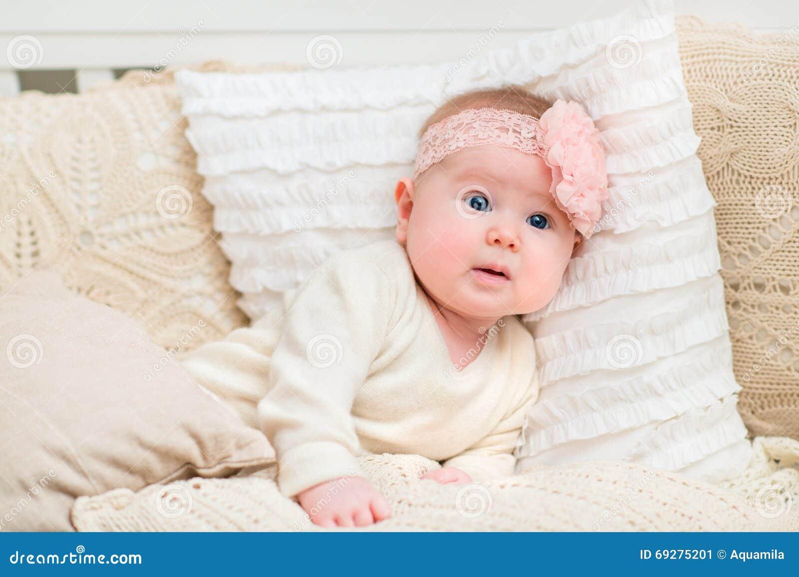 Έκπληκτο όμορφο κοριτσάκι με τα chubby μάγουλα και τα μεγάλα μπλε μάτια που φορούν τα άσπρα ενδύματα και ρόδινη ζώνη με το λουλού