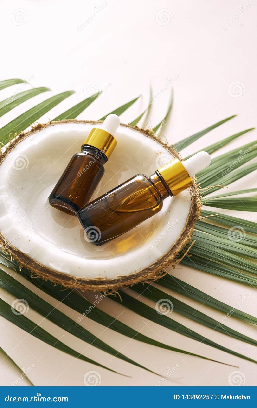 Έλαιο καρύδων στο μπουκάλι με τα ανοικτά καρύδια και πολτός στο βάζο, πράσινο υπόβαθρο φύλλων φοινικών Φυσικά καλλυντικά προϊόντα