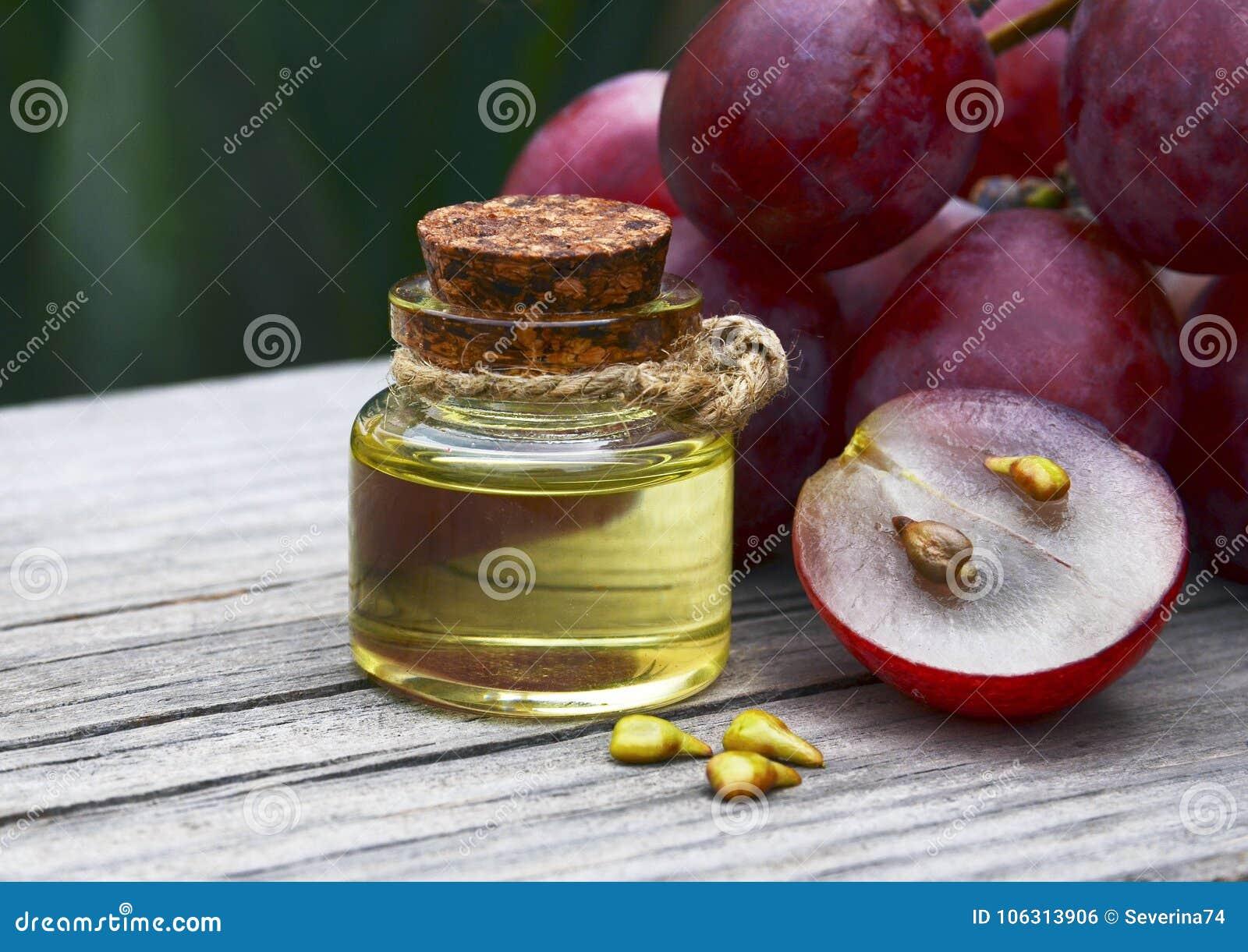 Έλαιο σπόρου σταφυλιών σε ένα βάζο γυαλιού και φρέσκα σταφύλια στον παλαιό ξύλινο πίνακα Μπουκάλι του οργανικού πετρελαίου σπόρου