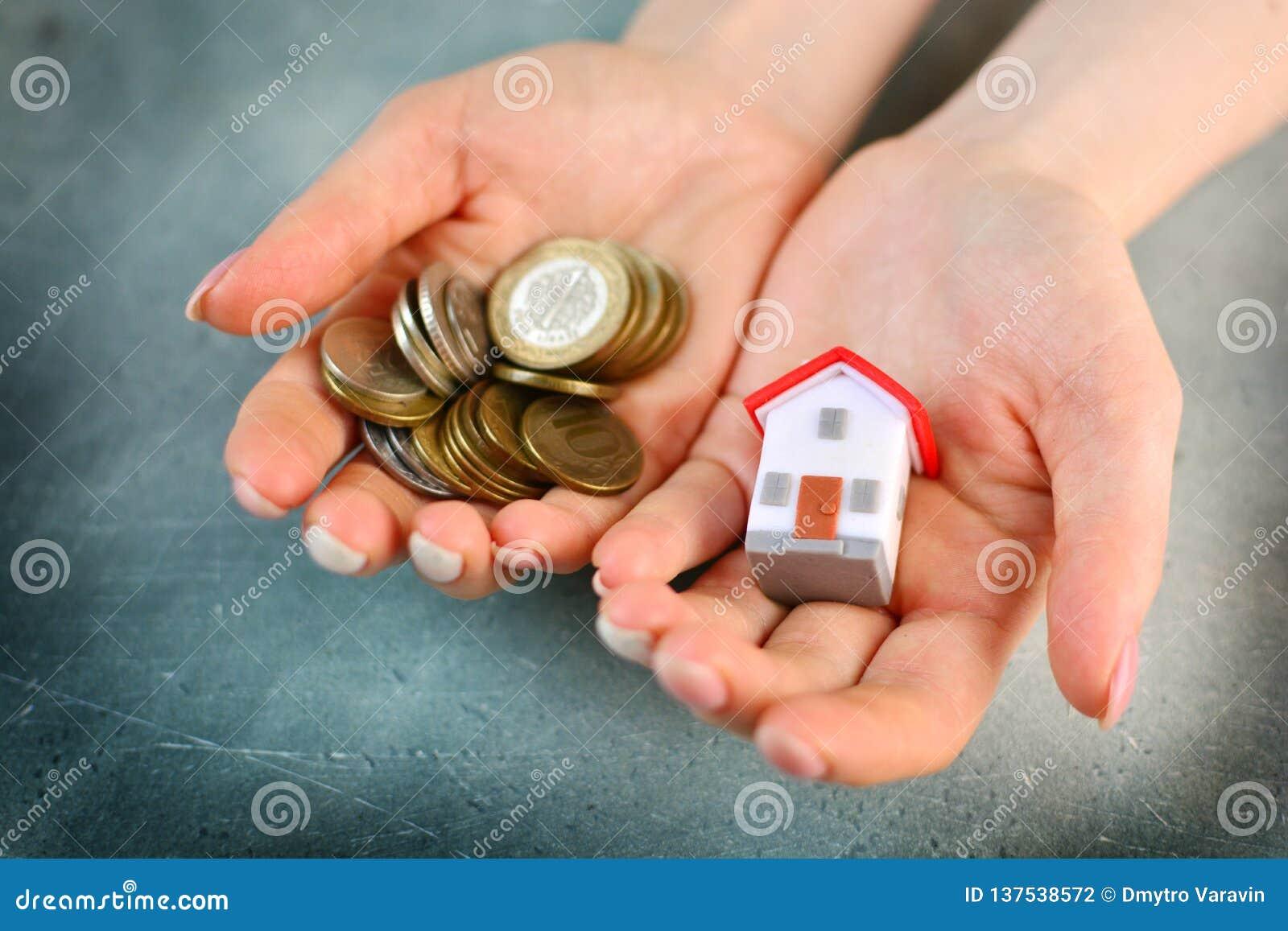 Έλλειψη χρημάτων για να αγοράσει μια έννοια σπιτιών Η γυναίκα κρατά το σπίτι παιχνιδιών σε μια χέρι και χούφτα των νομισμάτων σε
