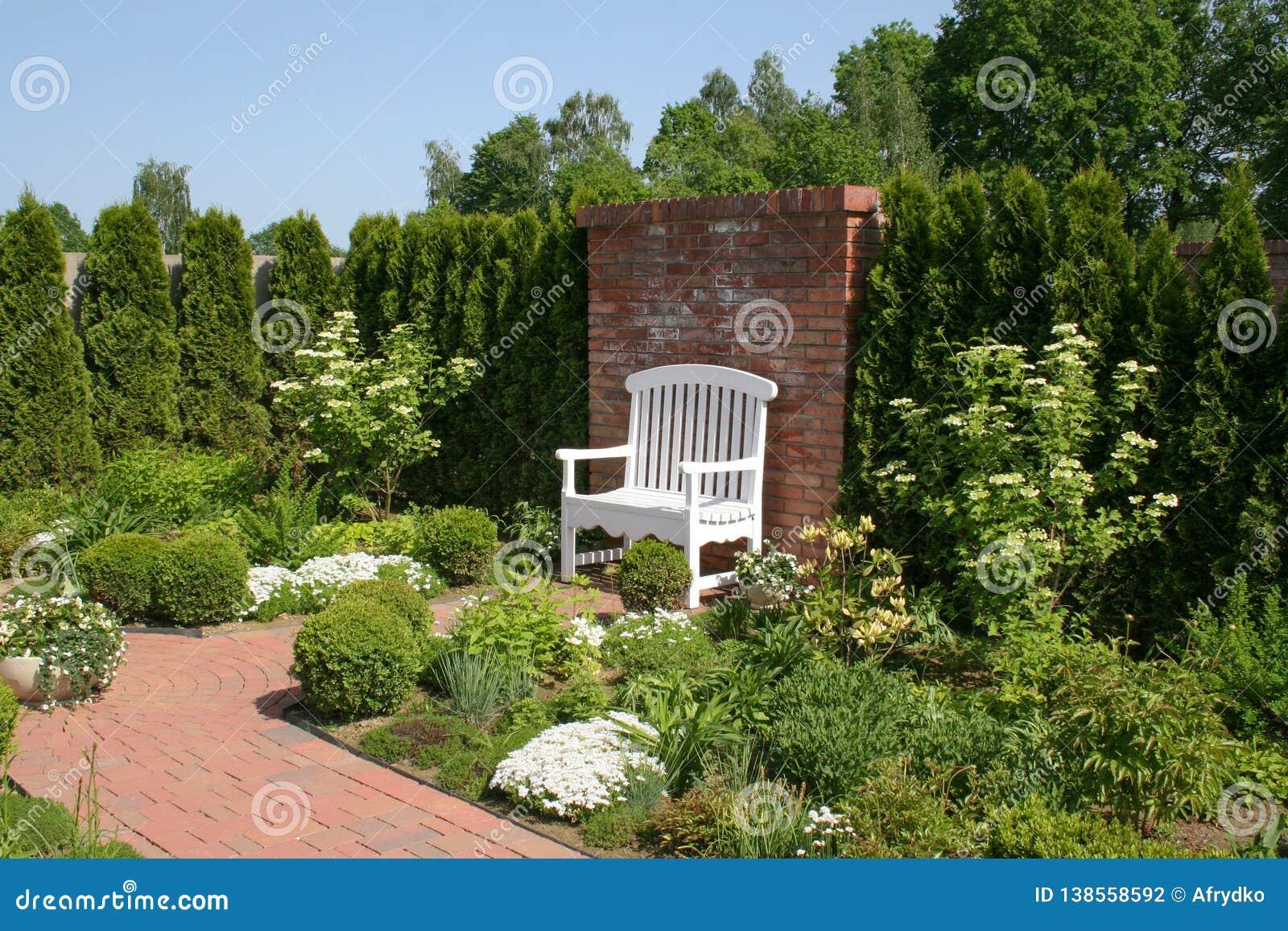 Ένας άσπρος διακοσμητικός πάγκος από έναν τουβλότοιχο που περιβάλλεται από έναν όμορφο ρομαντικό κήπο