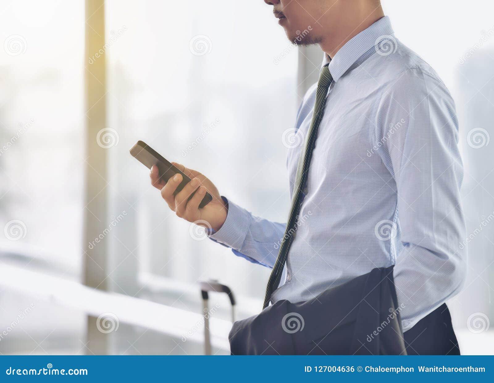 Ένας ασιατικός αρσενικός επιχειρηματίας χρησιμοποιεί ένα εξυπνώτερο τηλέφωνο στο communica