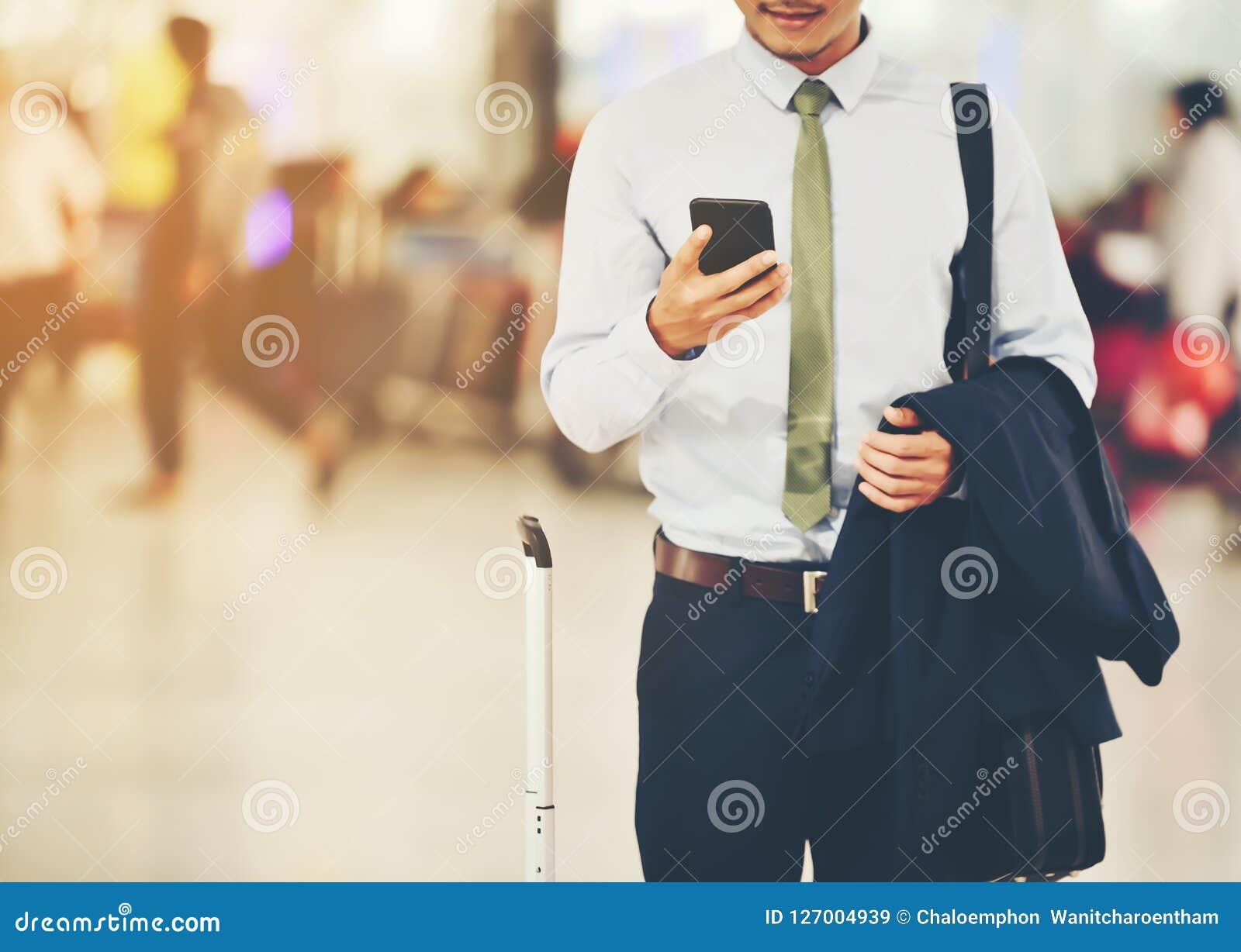 Ένας ασιατικός επιχειρηματίας χρησιμοποιεί ένα smartphone για να πάρει στην επιχείρηση wh