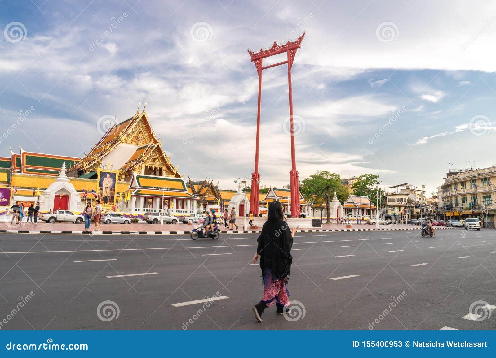 Ένας ασιατικός τουρίστας περπατά κατά μήκος της οδού στη γιγαντιαίο ταλάντευση ή το Σάο Ching Cha το ορόσημο της πόλης της Μπανγκ