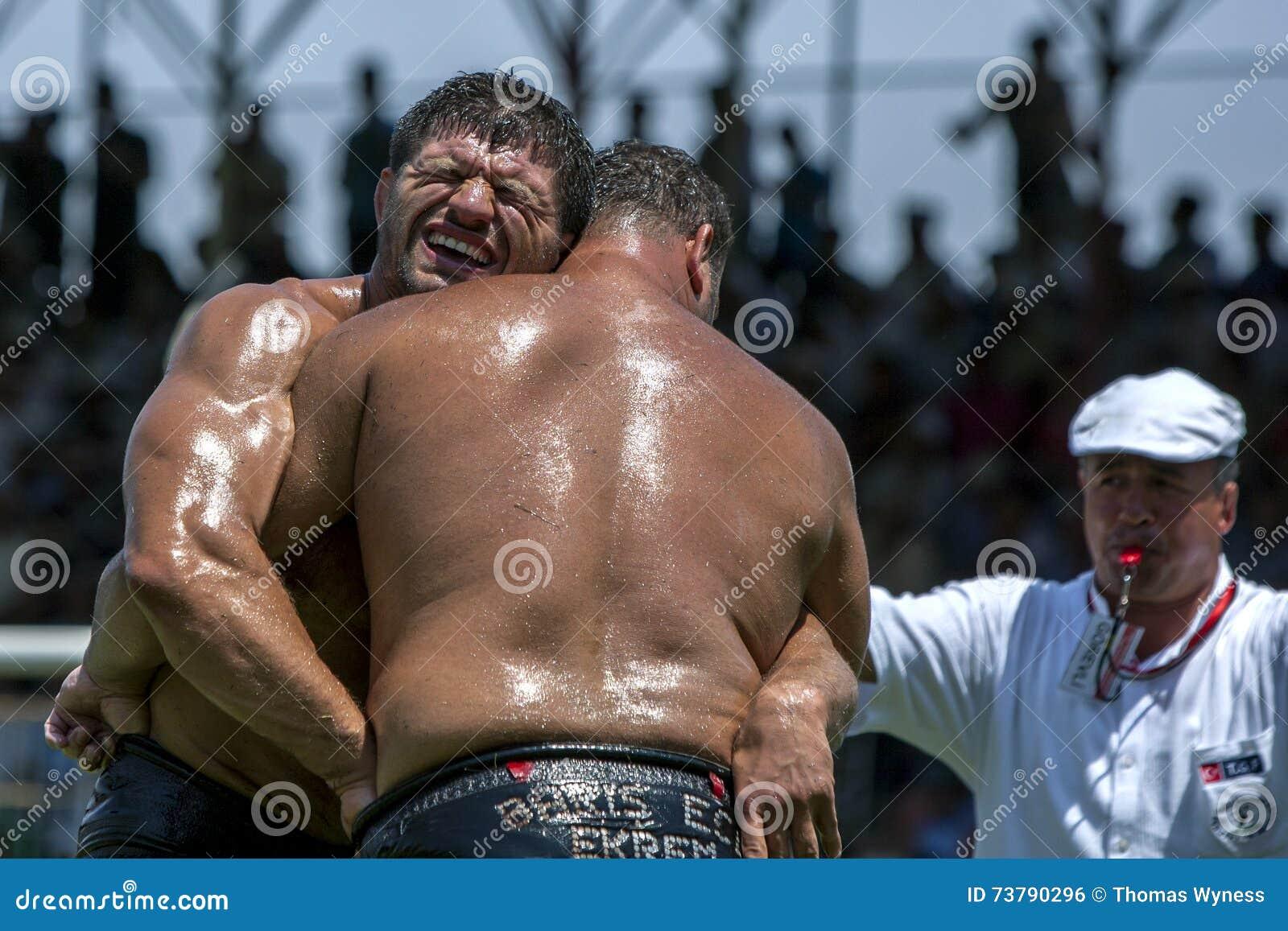 Ένας βαρέων βαρών παλαιστής μορφάζει ταυτόχρονα ανταγωνιστικός στο τουρκικό φεστιβάλ πάλης πετρελαίου Elmali σε Elmali, Τουρκία