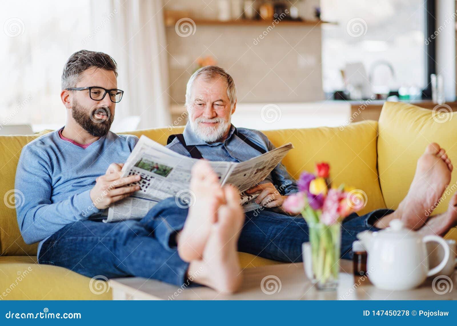 Ένας ενήλικος γιος hipster και μια ανώτερη συνεδρίαση πατέρων στον καναπέ στο εσωτερικό στο σπίτι, ομιλία
