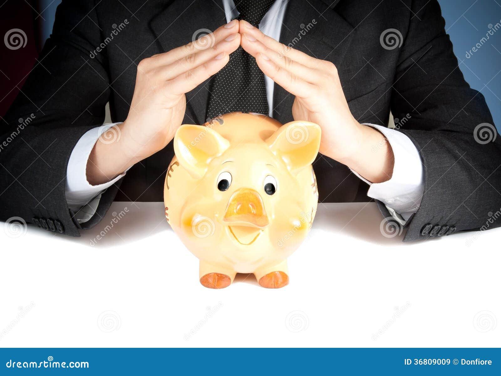 Ένας επιχειρηματίας κάνει με το χέρι του ένα σπίτι πίσω από μια piggy τράπεζα, έννοια για την επιχείρηση και κερδίζει χρήματα