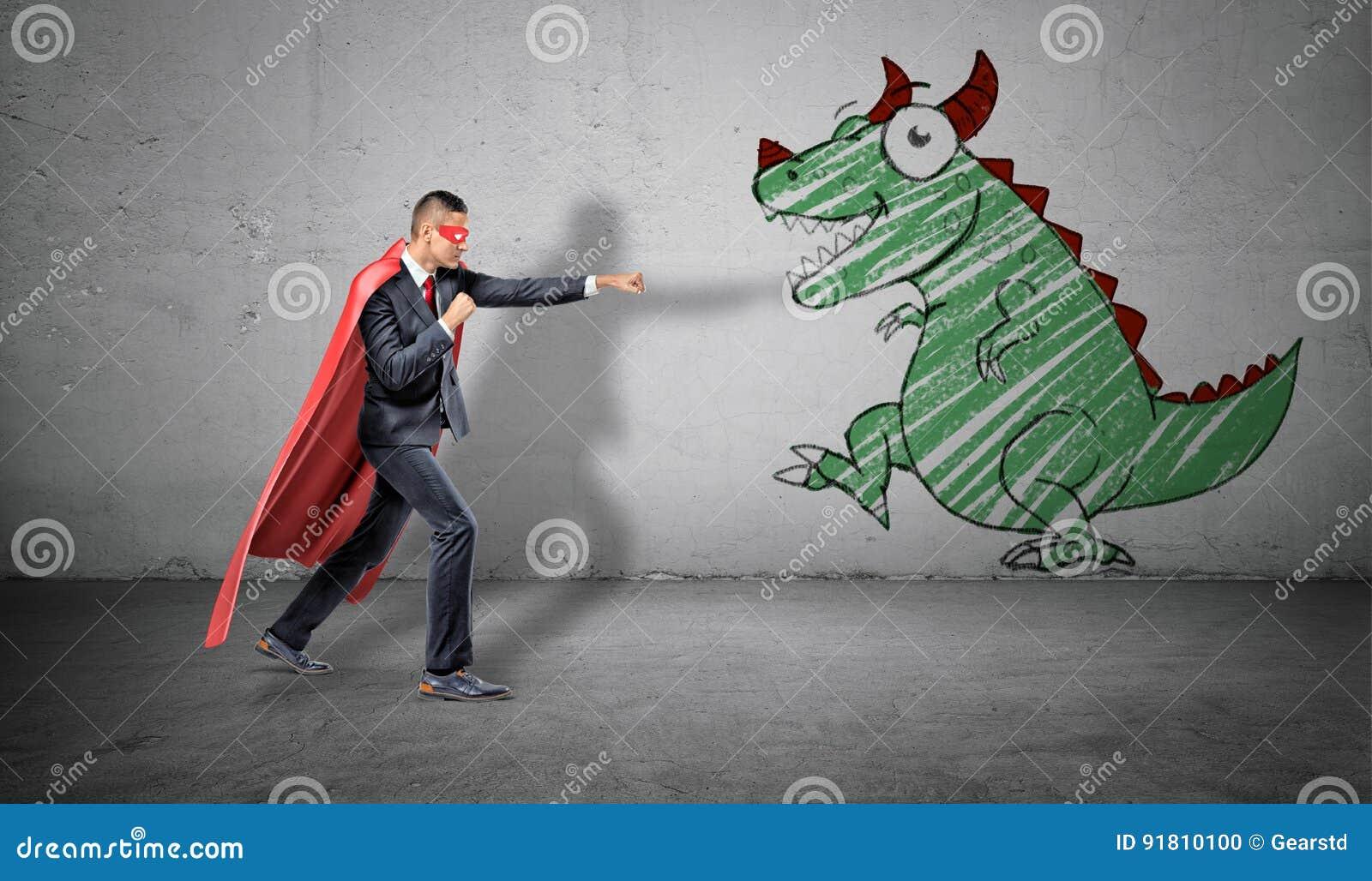 Ένας επιχειρηματίας σε ένα κόκκινο ακρωτήριο που στέκεται στην πάλη θέτει έτοιμο να παλεψει μια εικόνα ενός δράκου στον κοντινότε