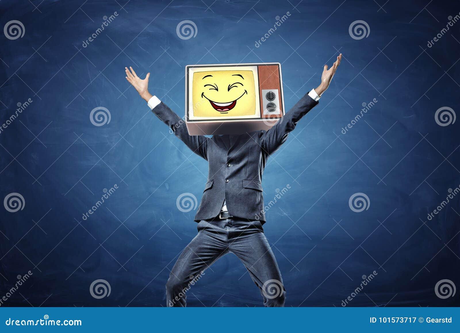 Ένας ευτυχής επιχειρηματίας με τα χέρια που αυξάνονται στη νίκη έχει μια αναδρομική TV με ένα κίτρινο πρόσωπο smiley αντί του κεφ