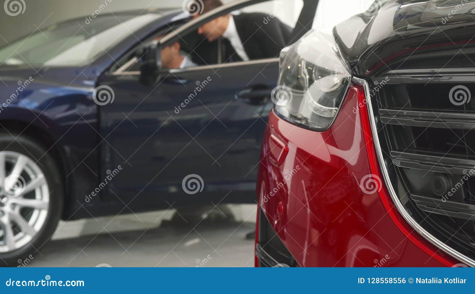 Ένας καλός πωλητής αυτοκινήτων οδηγεί τον πελάτη στο αυτοκίνητό του