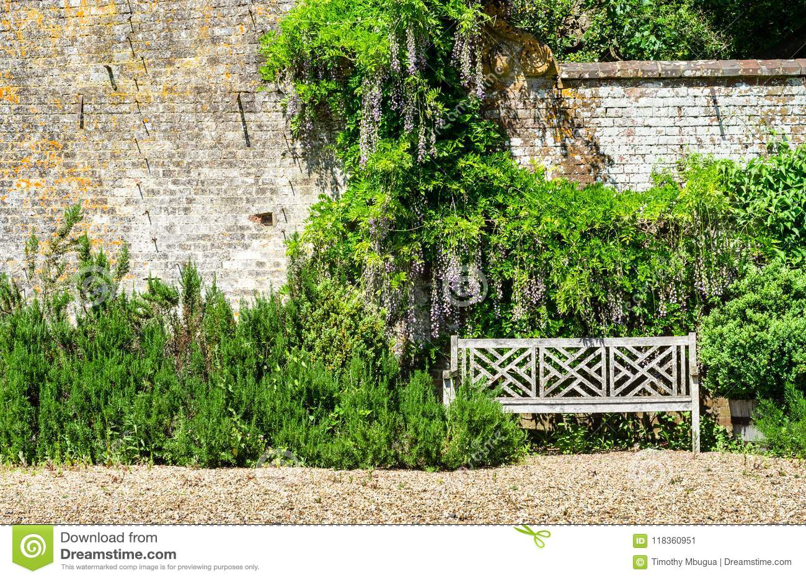 Ένας κενός ξύλινος πάγκος από έναν τοίχο κήπων