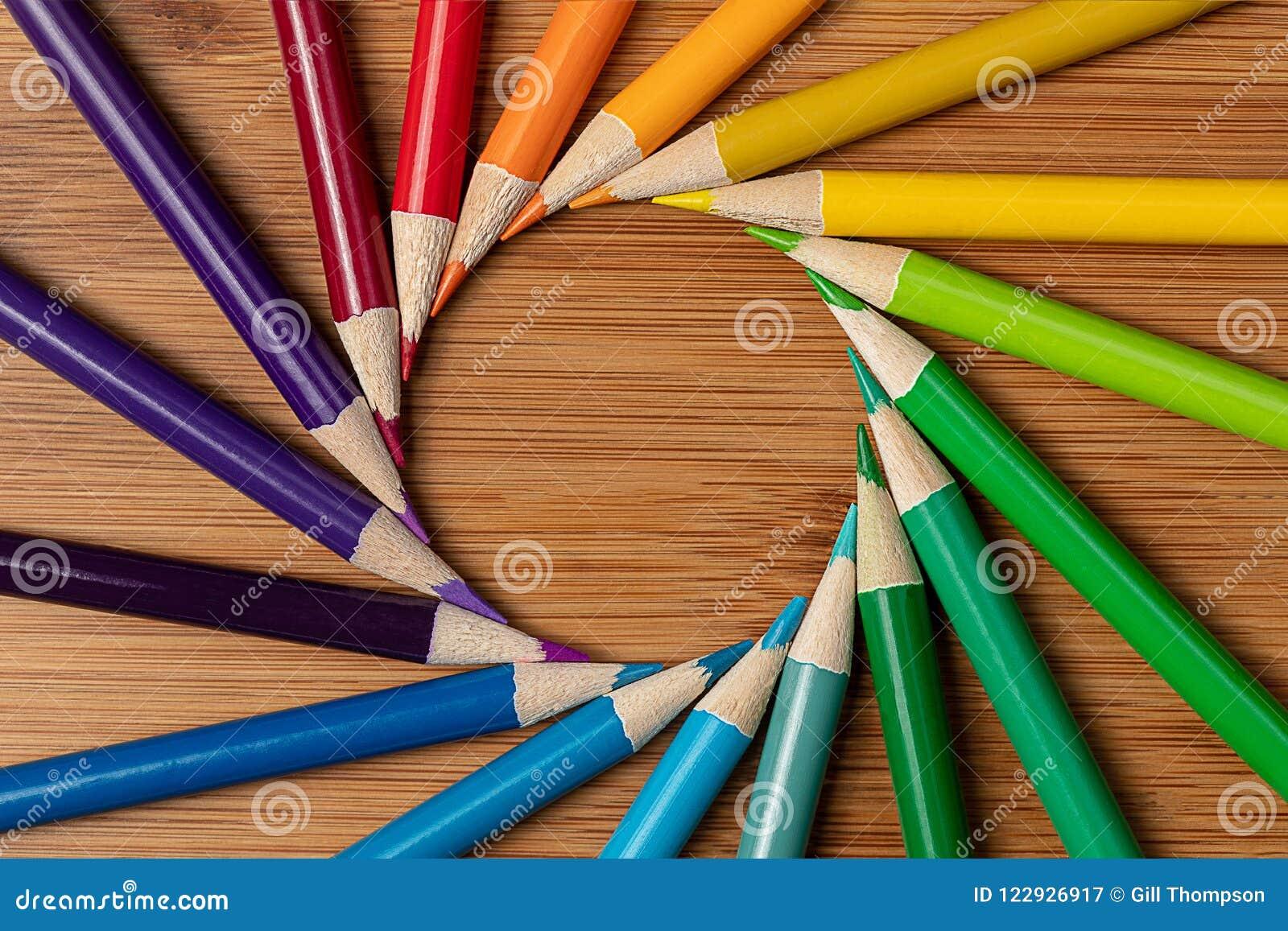 Ένας μακρο πυροβολισμός των ακονισμένων χρωματισμένων μολυβιών σε ένα σπειροειδές ελαφρύ κτύπημα δίνης