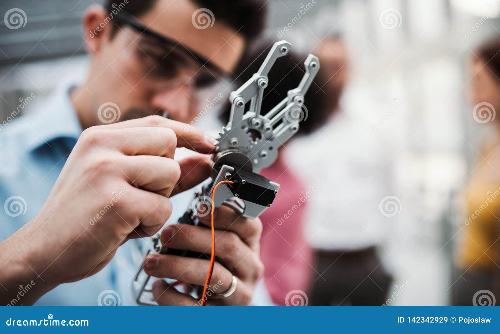 Ένας νέος επιχειρηματίας ή ένας επιστήμονας με τη ρομποτική στάση χεριών στην αρχή, εργασία