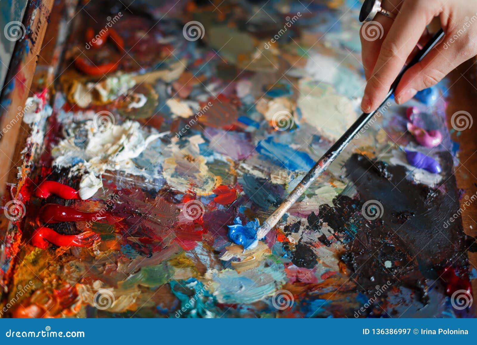 Ένας νέος καλλιτέχνης γυναικών χρωματίζει μια ελαιογραφία easel