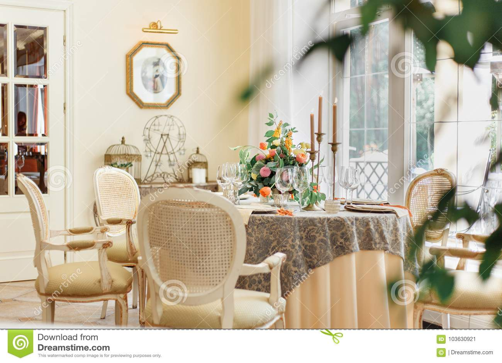Ένας να δειπνήσει πίνακας και άνετες πολυθρόνες σε ένα σύγχρονο σπίτι με μια ελαφριά τραπεζαρία