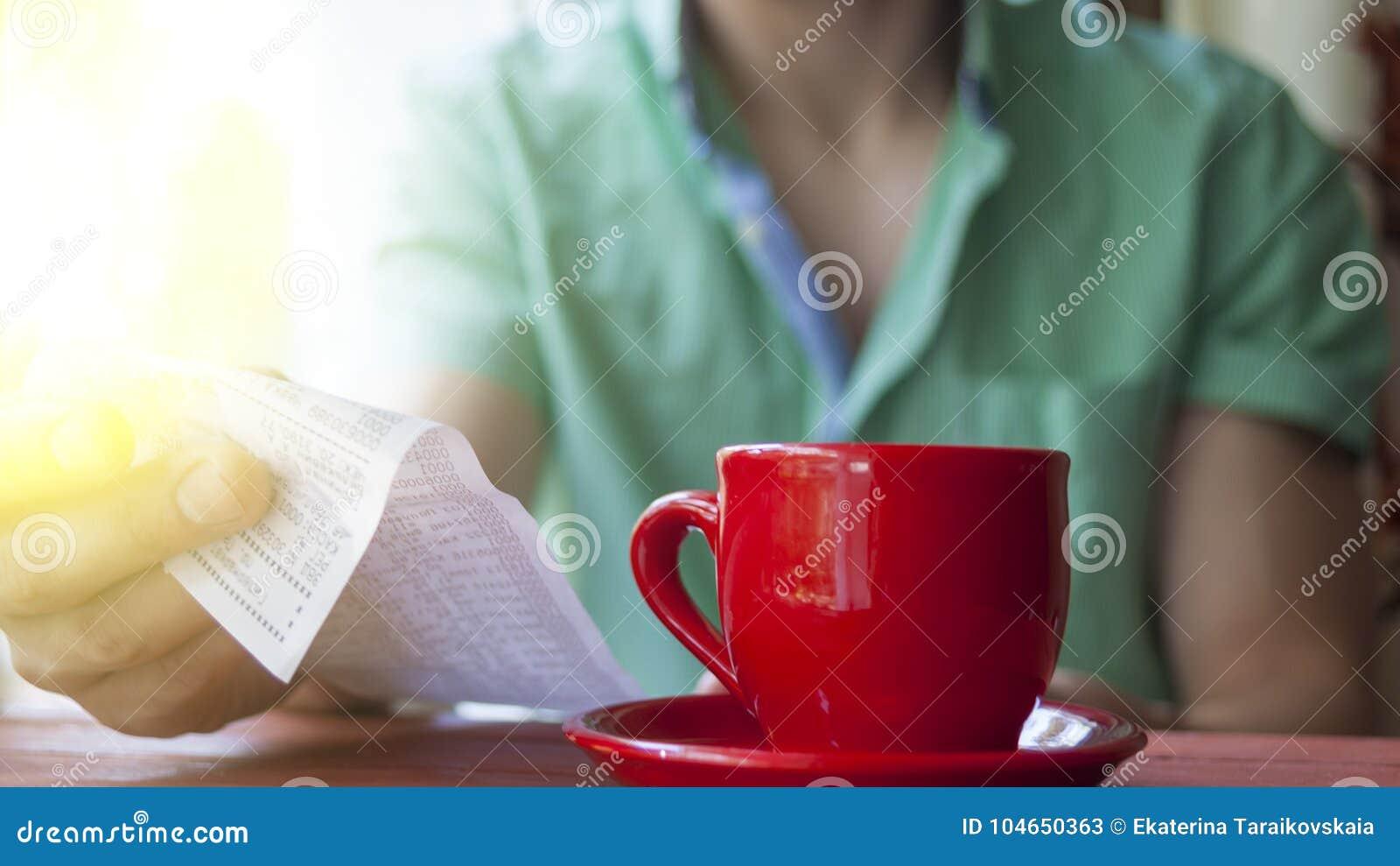 Ένας νεαρός άνδρας εξετάζει το λογαριασμό σε έναν καφέ σε ένα ηλιόλουστο θερινό πρωί