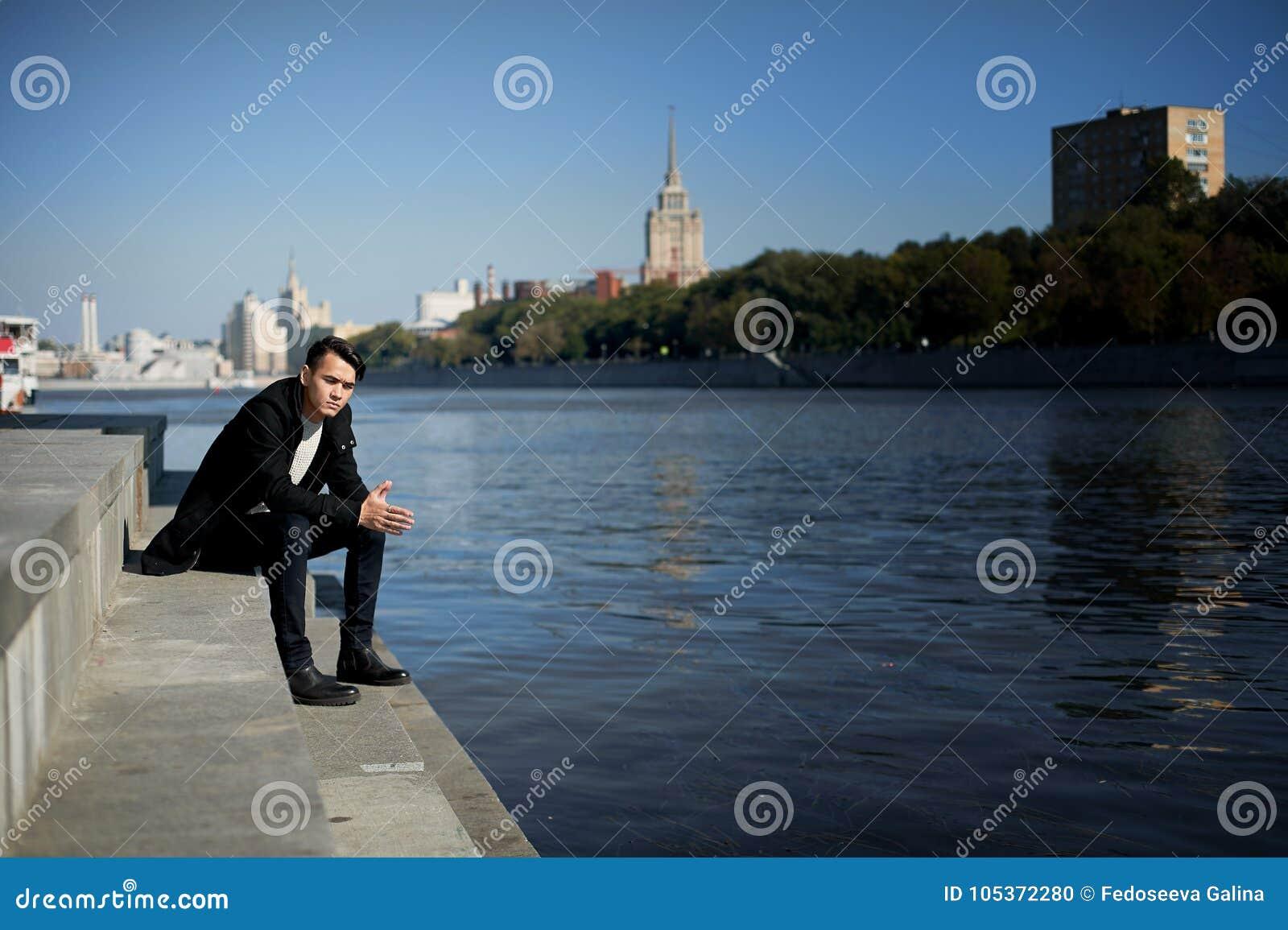 Ένας νεαρός άνδρας, λεπταίνει Με τη σκοτεινή τρίχα και τα καφετιά μάτια Κάθισμα στα βήματα κοντά στο νερό Λυπημένος αστικό διάνυσ