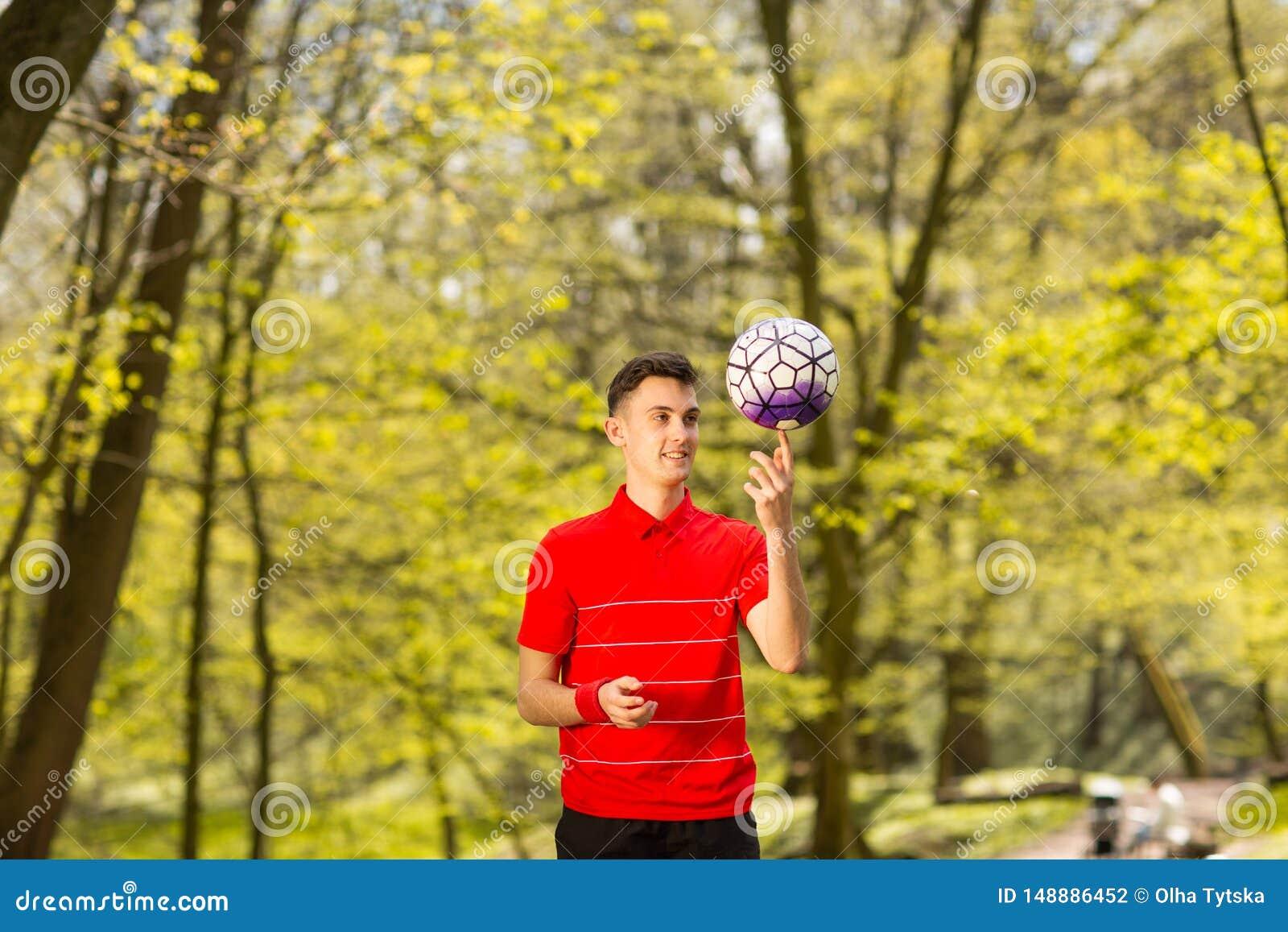 Ένας νεαρός άνδρας παιχνίδια στα κόκκινα μπλουζών με μια σφαίρα ποδοσφαίρου στο πράσινο πάρκο r