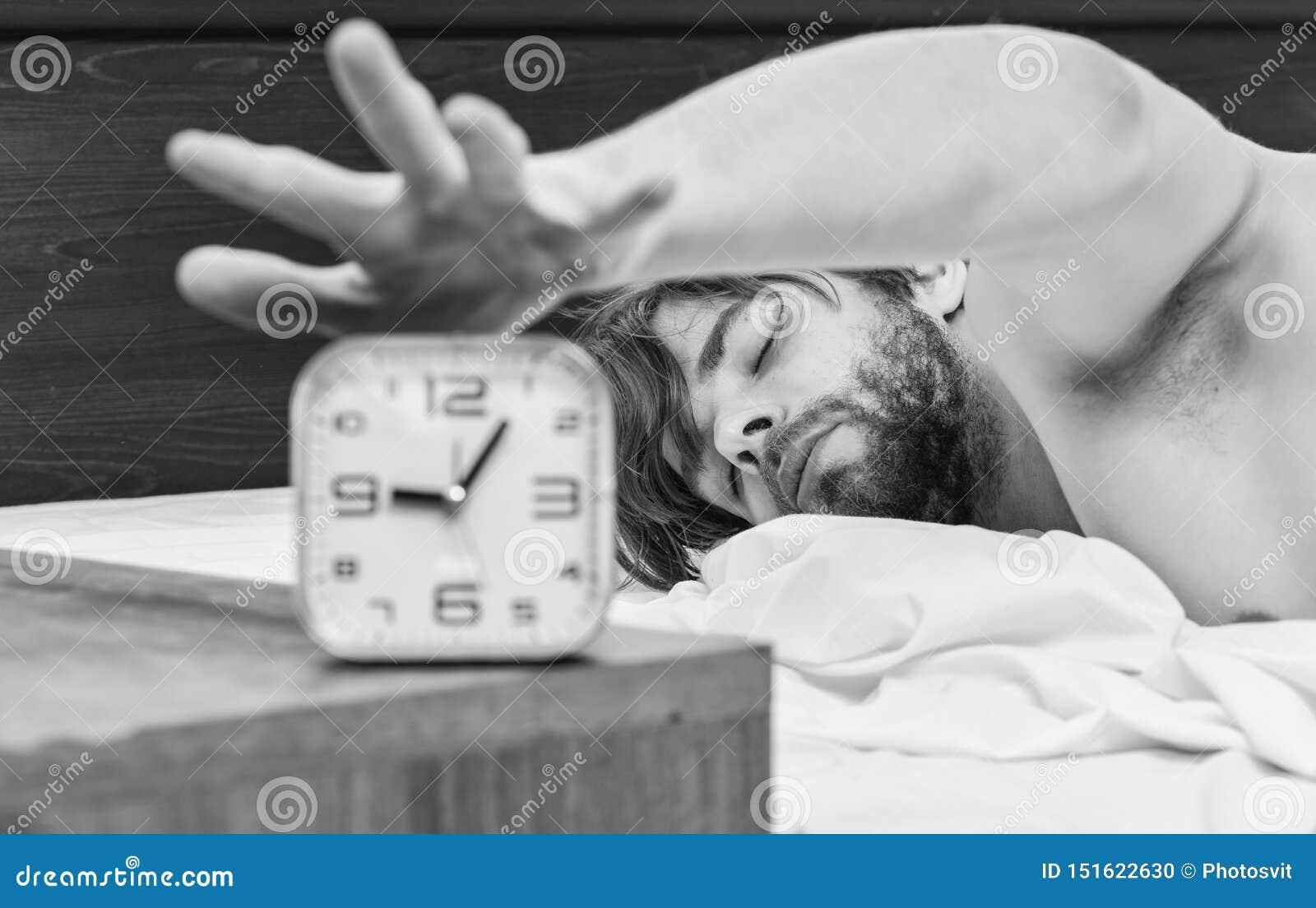 Ένας νεαρός άνδρας που ξυπνά στο κρεβάτι και που τεντώνει τα όπλα του E Ξυπνήστε άτομα πρωινού