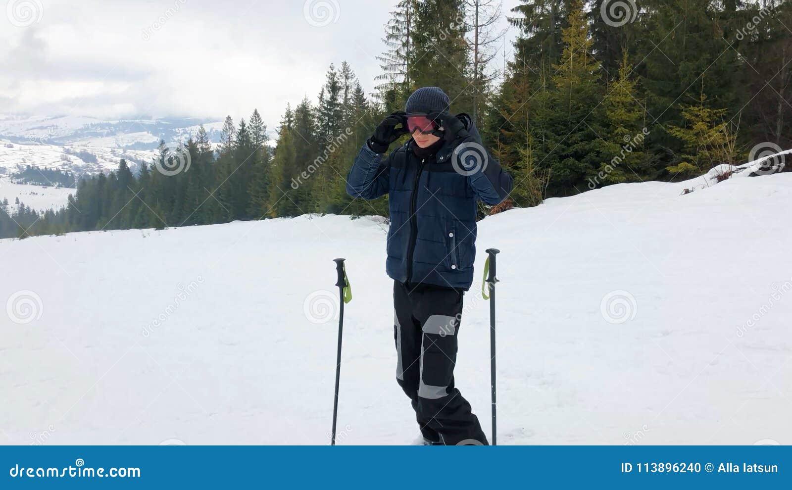 Ένας νεαρός άνδρας στα αθλητικά γυαλιά κάνει σκι στα βουνά