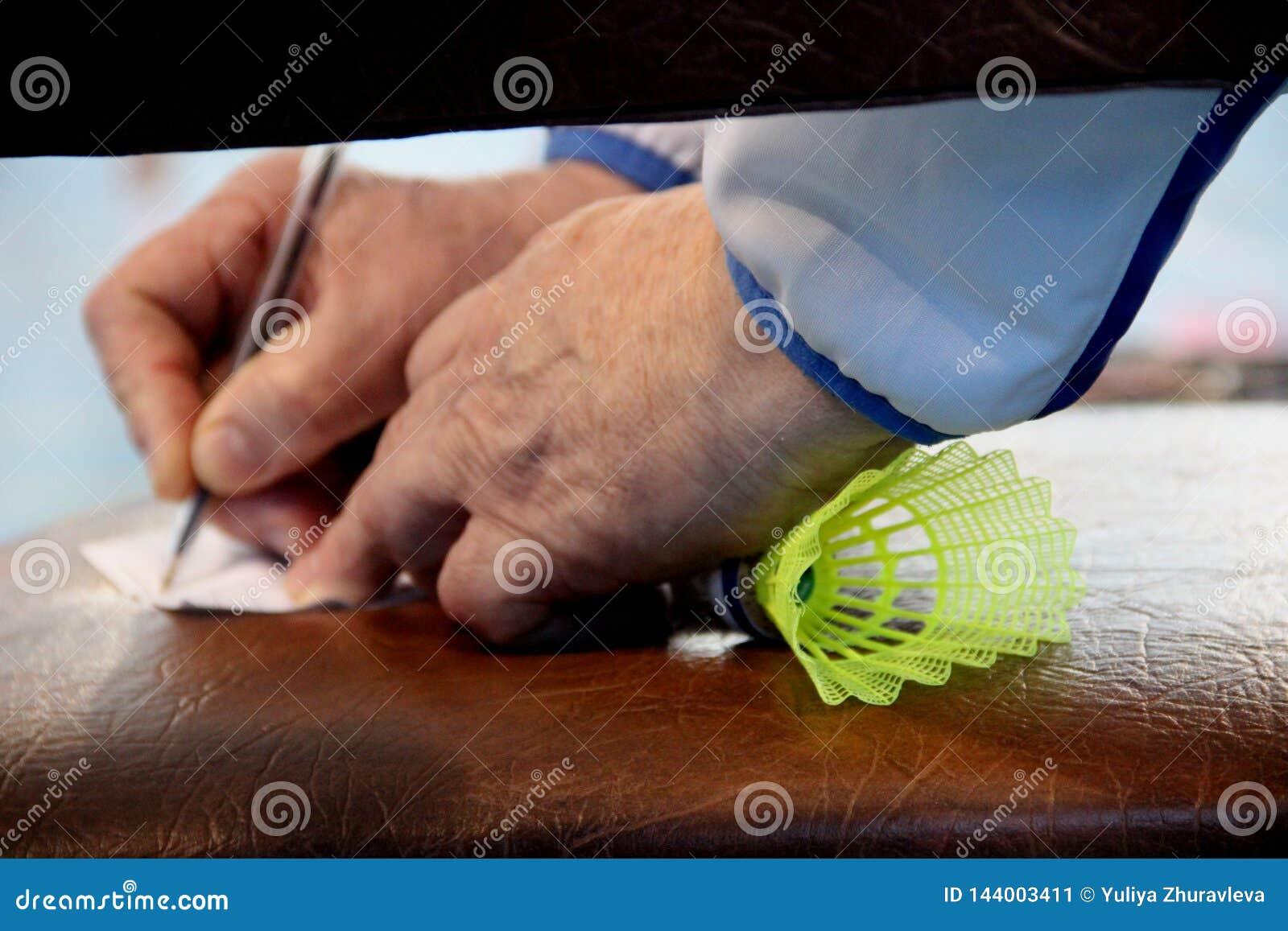 ένας παλαιότερος εκπαιδευτής παίρνει τις σημειώσεις με ένα shuttlecock για το μπάντμιντον στην πυγμή του, που πλαισιώνει την κινη