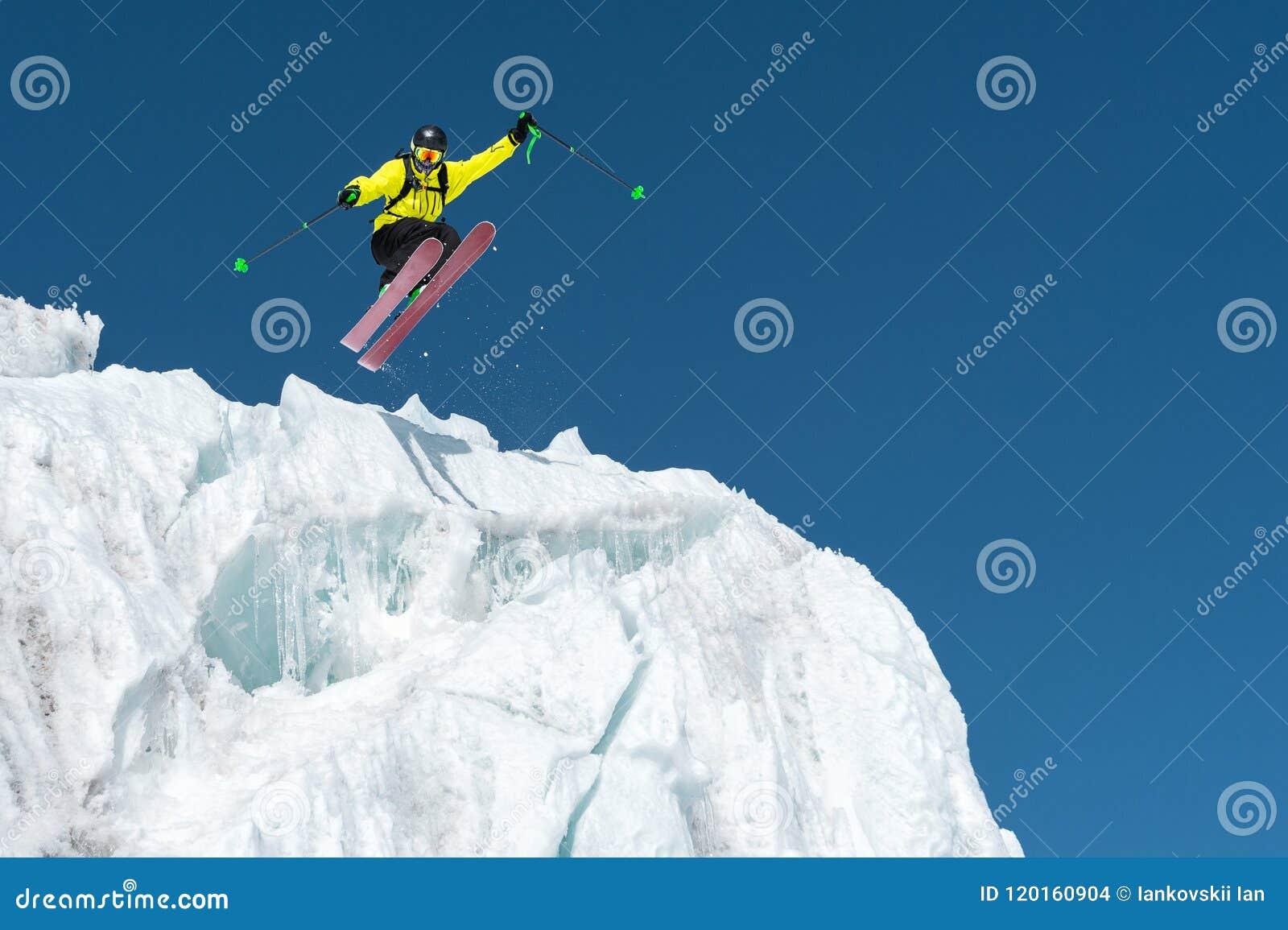 Ένας πηδώντας σκιέρ που πηδά από έναν παγετώνα ενάντια σε έναν μπλε ουρανό - υψηλό στα βουνά Επαγγελματικό να κάνει σκι