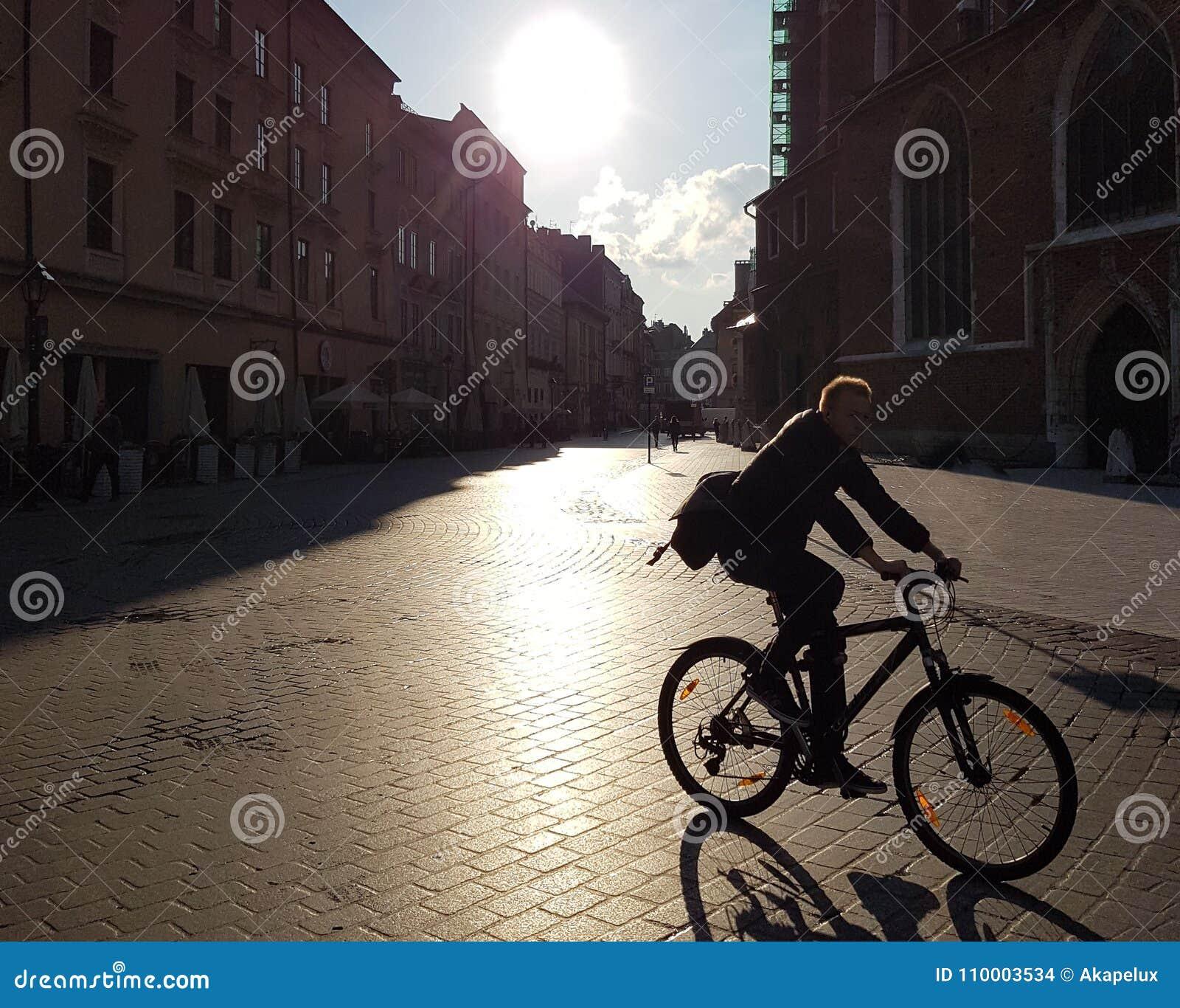 Ένας ποδηλάτης με οδηγά μέσω Follow! Ένας ποδηλάτης οδηγά μέσω της πόλης στο φως πρωινού πόλη στο φως πρωινού
