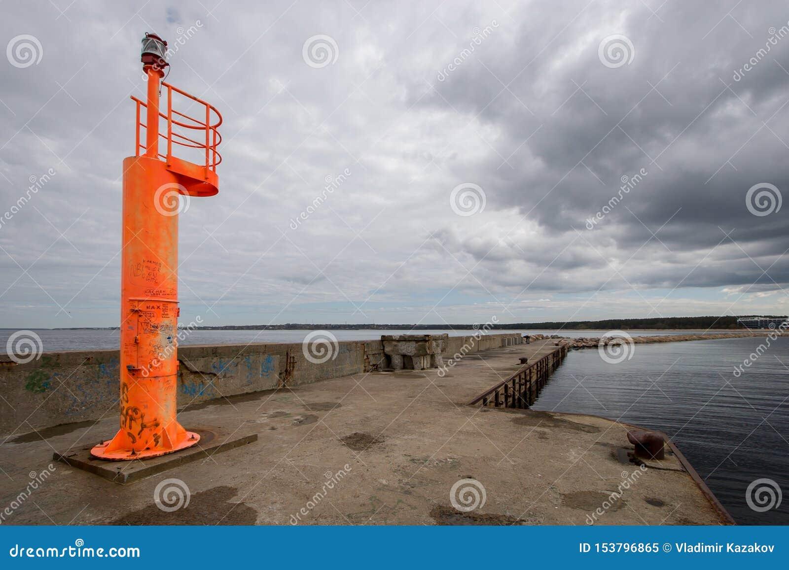 Ένας πορτοκαλής φάρος στέκεται σε μια συγκεκριμένη αποβάθρα στο υπόβαθρο ενός σκοτεινού ουρανού με τα σύννεφα