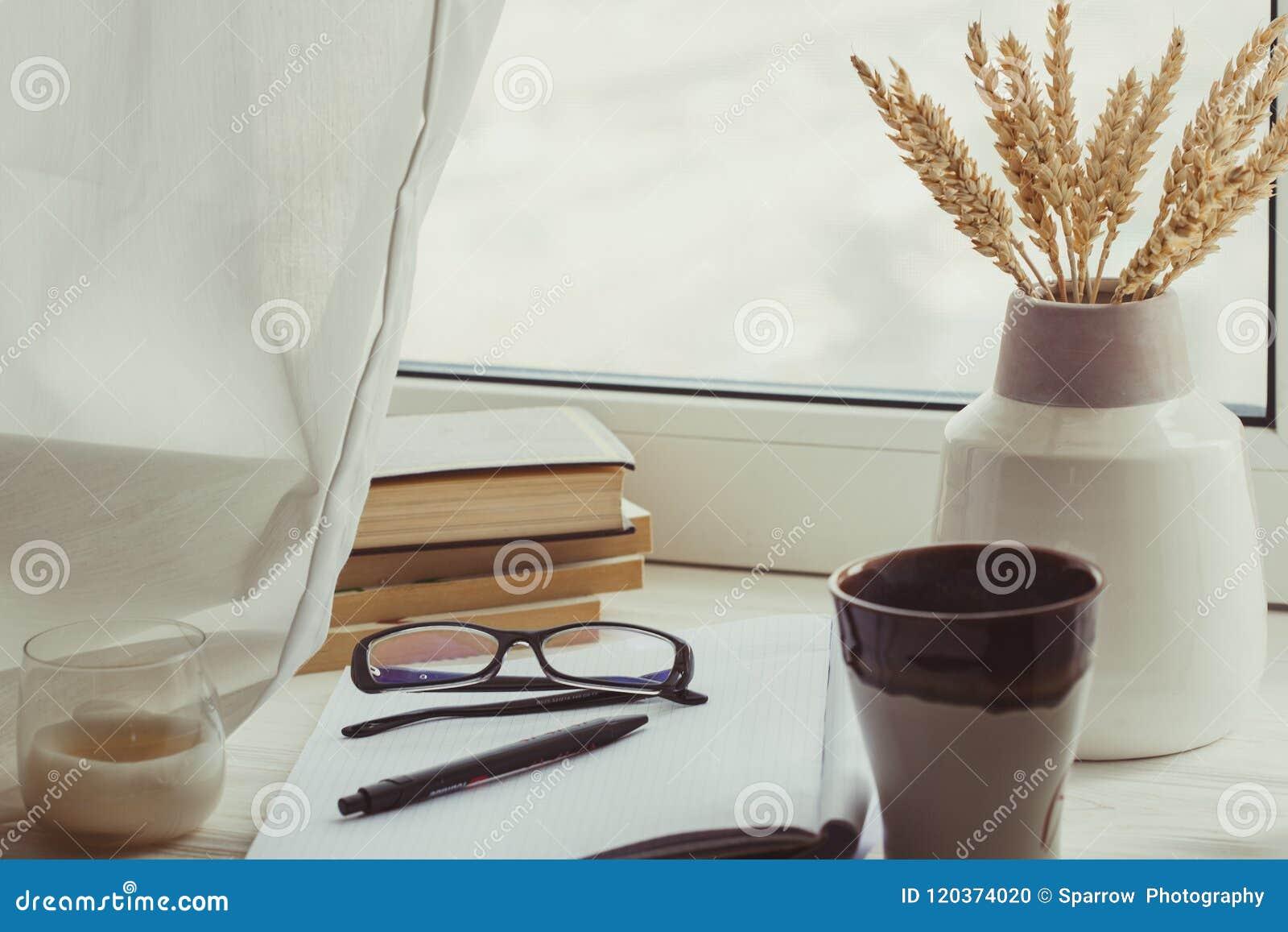Ένας σωρός των βιβλίων, φλιτζάνι του καφέ, ανθοδέσμη των πυρήνων, των γυαλιών, του σημειωματάριου και της μάνδρας πέρα από ένα πα