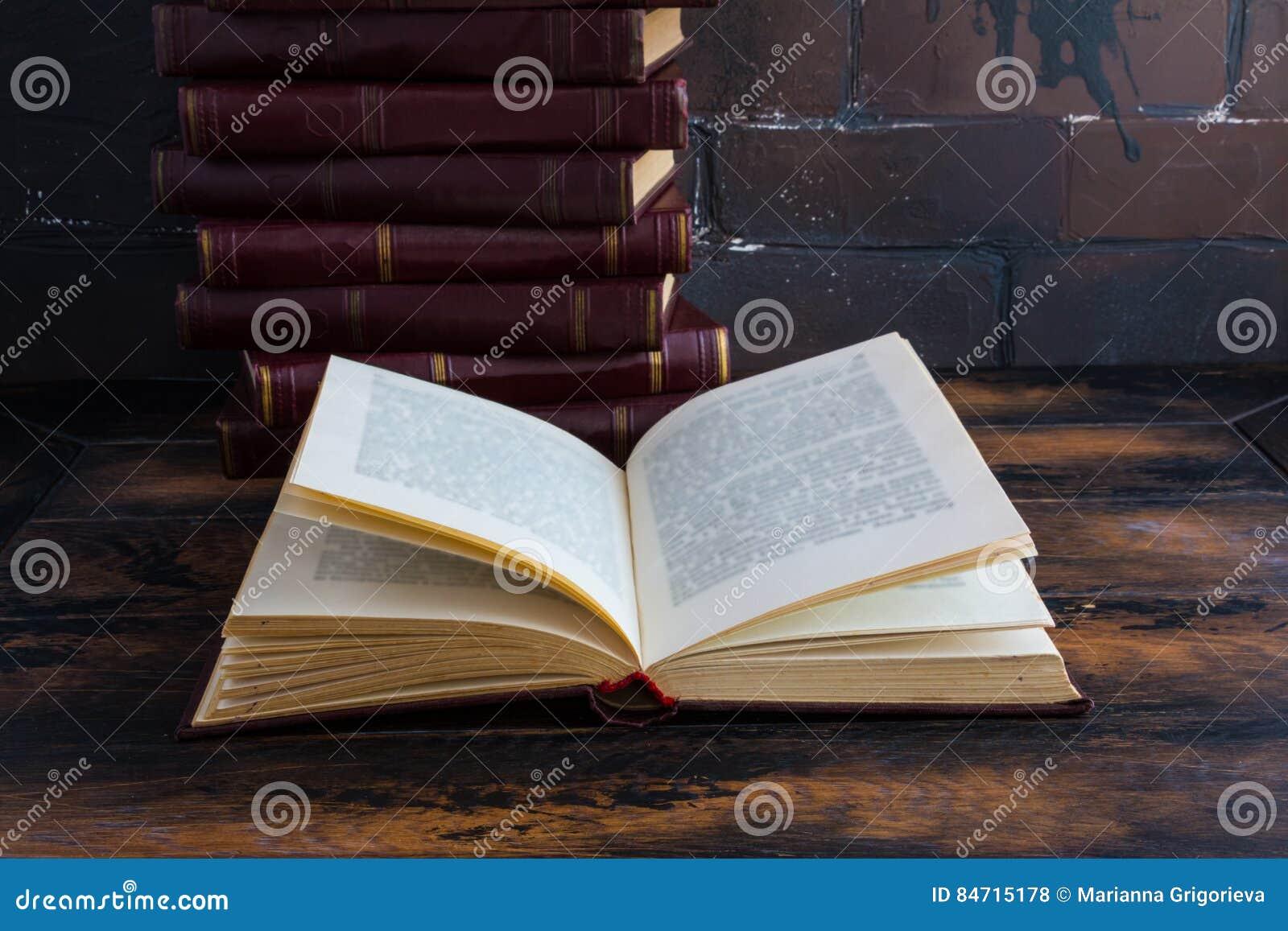 Ένας σωρός των βιβλίων με μια σκούρο κόκκινο σκληρή κάλυψη ένα μια άλλη και το ανοικτό βιβλίο σε έναν ξύλινο πίνακα στα πλαίσια τ