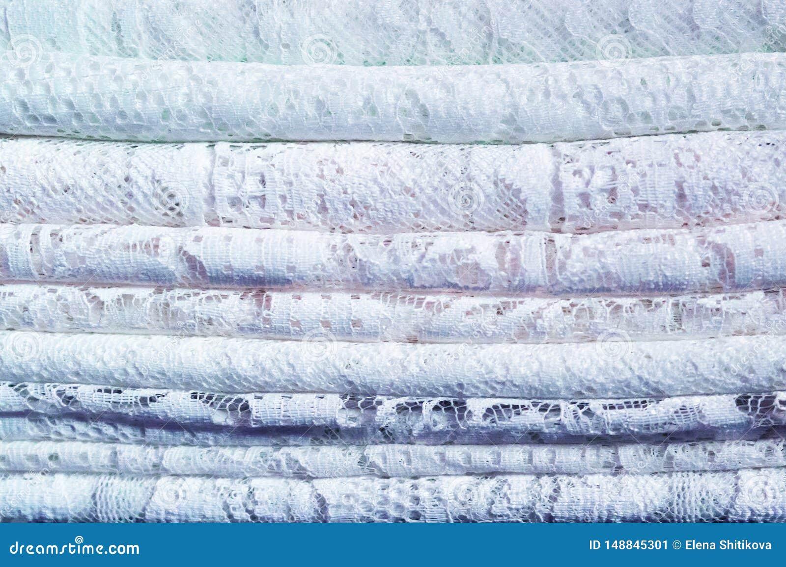 Ένας σωρός των λεπτών παραδοσιακών υφαντικών υφασμάτων δαντελλών με ένα φυσικό σχέδιο άσπρος και μπλε