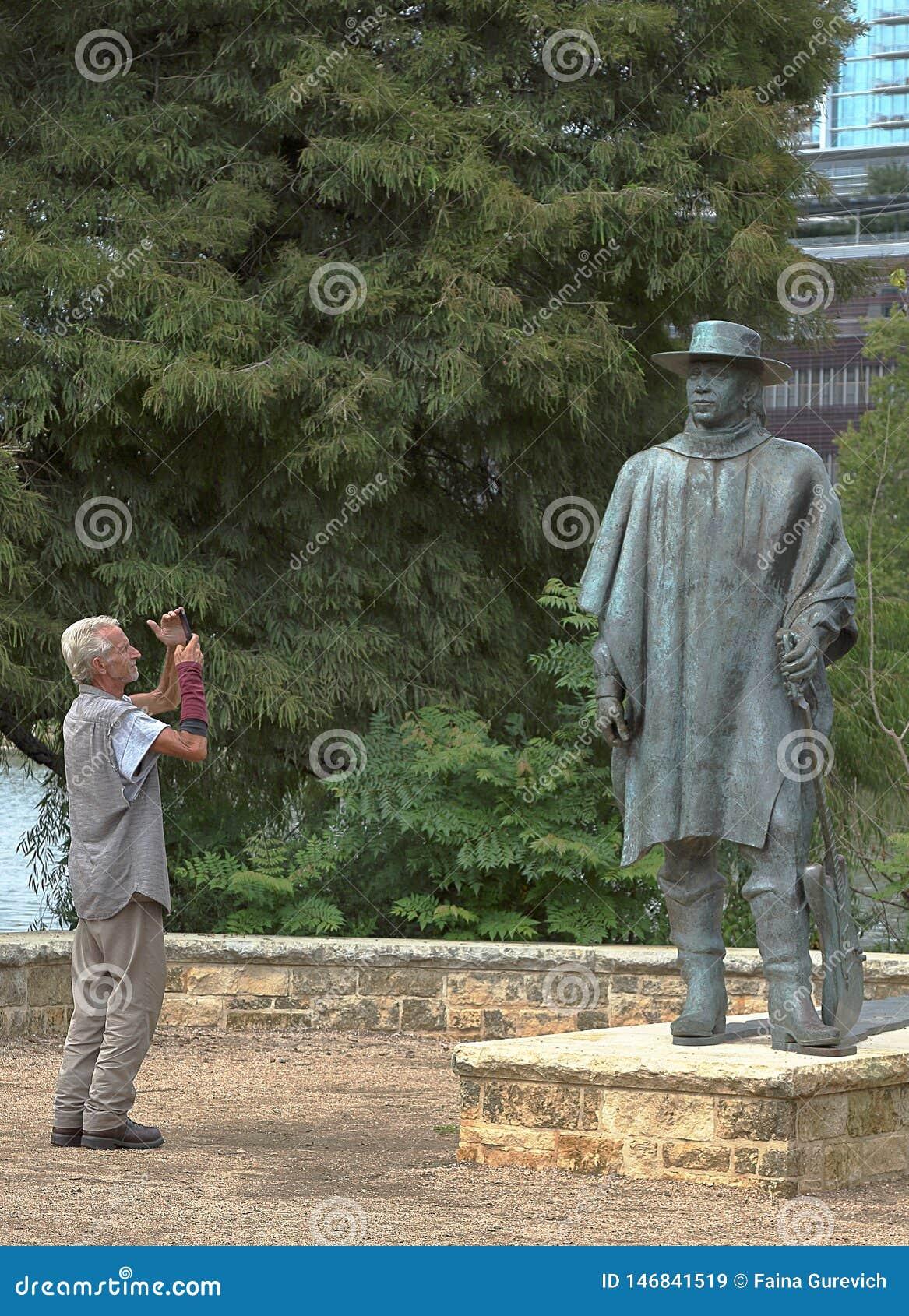 Ένας τουρίστας που παίρνει την εικόνα του αγάλματος της Stevie Ray Vaughan, εργασία από το Ralph Helmick, στο Ώστιν, Τέξας