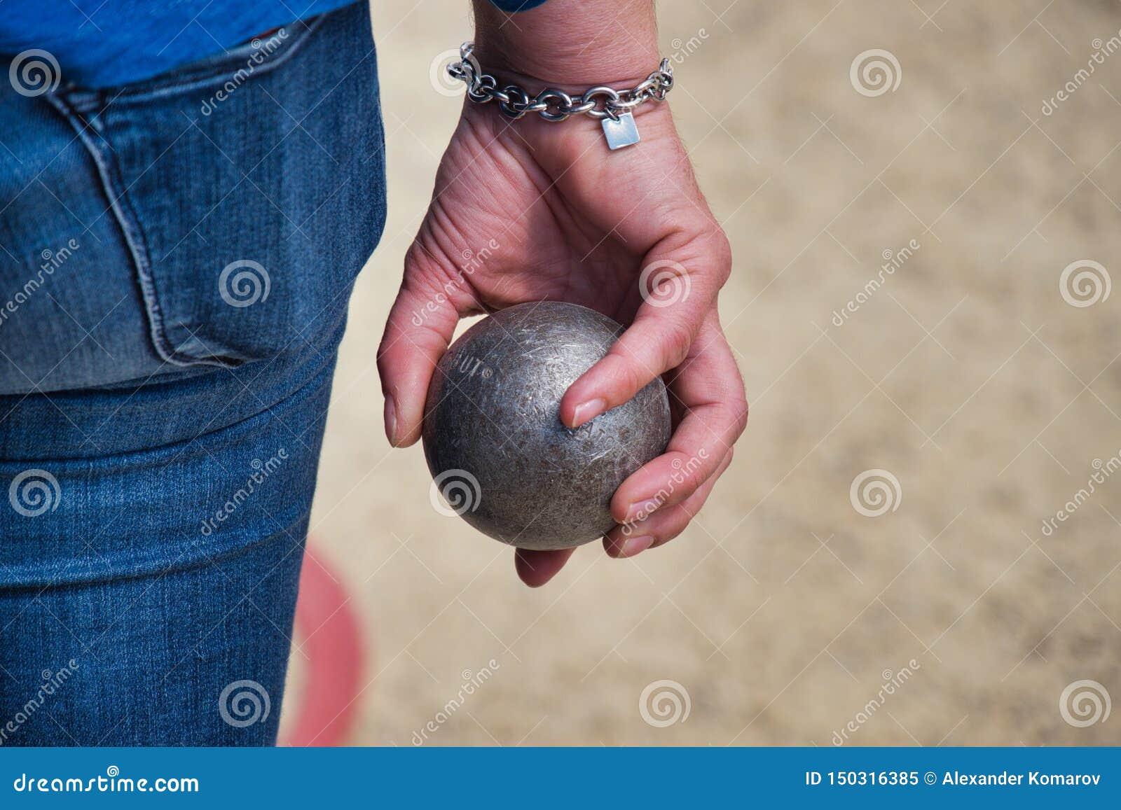 Ένας φορέας κρατά υπό εξέταση ένα boule για το petanque