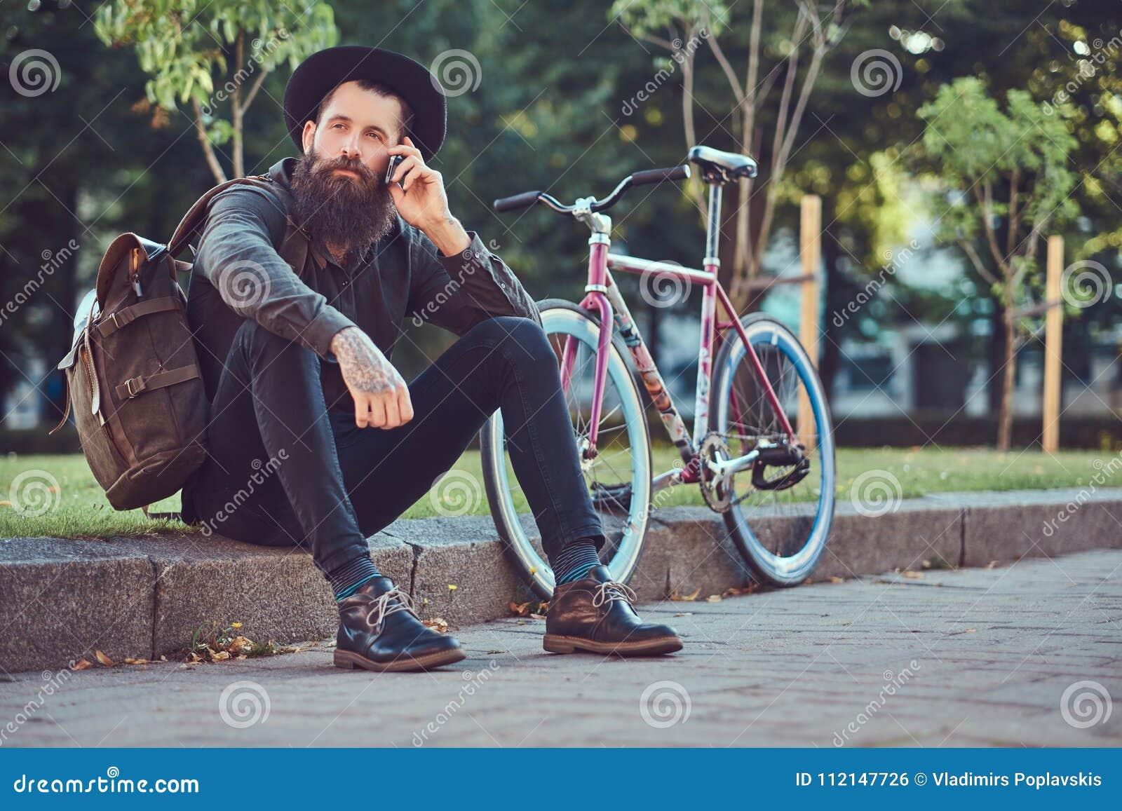Ένας όμορφος ταξιδιώτης hipster με μια μοντέρνη γενειάδα και δερματοστιξία στα όπλα του που ντύνονται στα περιστασιακά ενδύματα κ