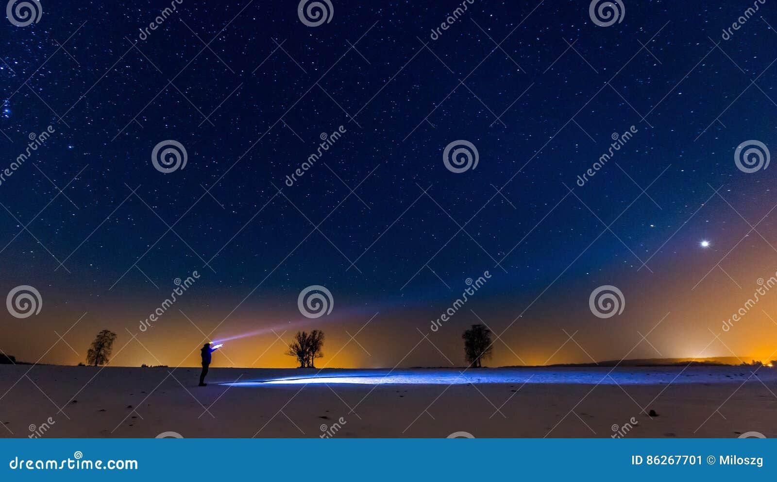 Έναστροι ουρανός και άτομο με το φακό να είστε μπορεί να σχεδιάσει το χρησιμοποιημένο νύχτα χειμώνα τοπίων απεικόνισής σας