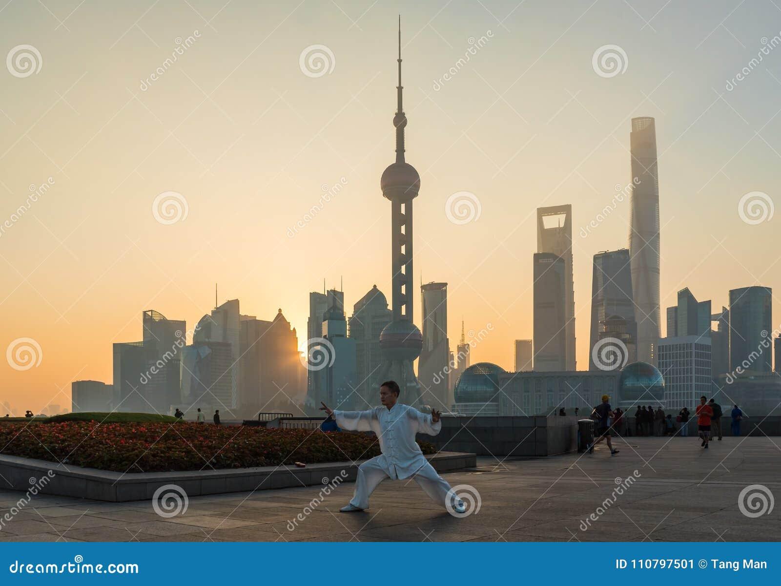 Ένα άτομο ασκεί και κάνει Tai Chi στο φράγμα καθώς ο ήλιος αυξάνεται