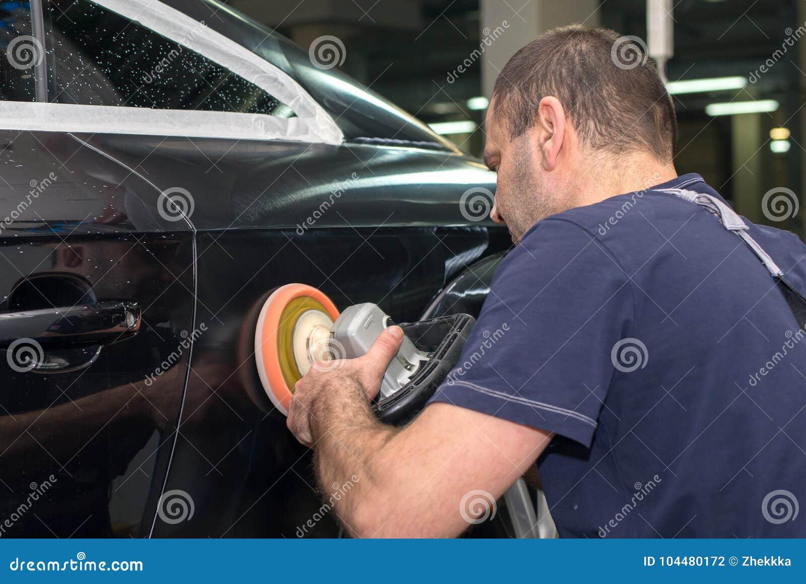 Ένα άτομο γυαλίζει ένα μαύρο αυτοκίνητο