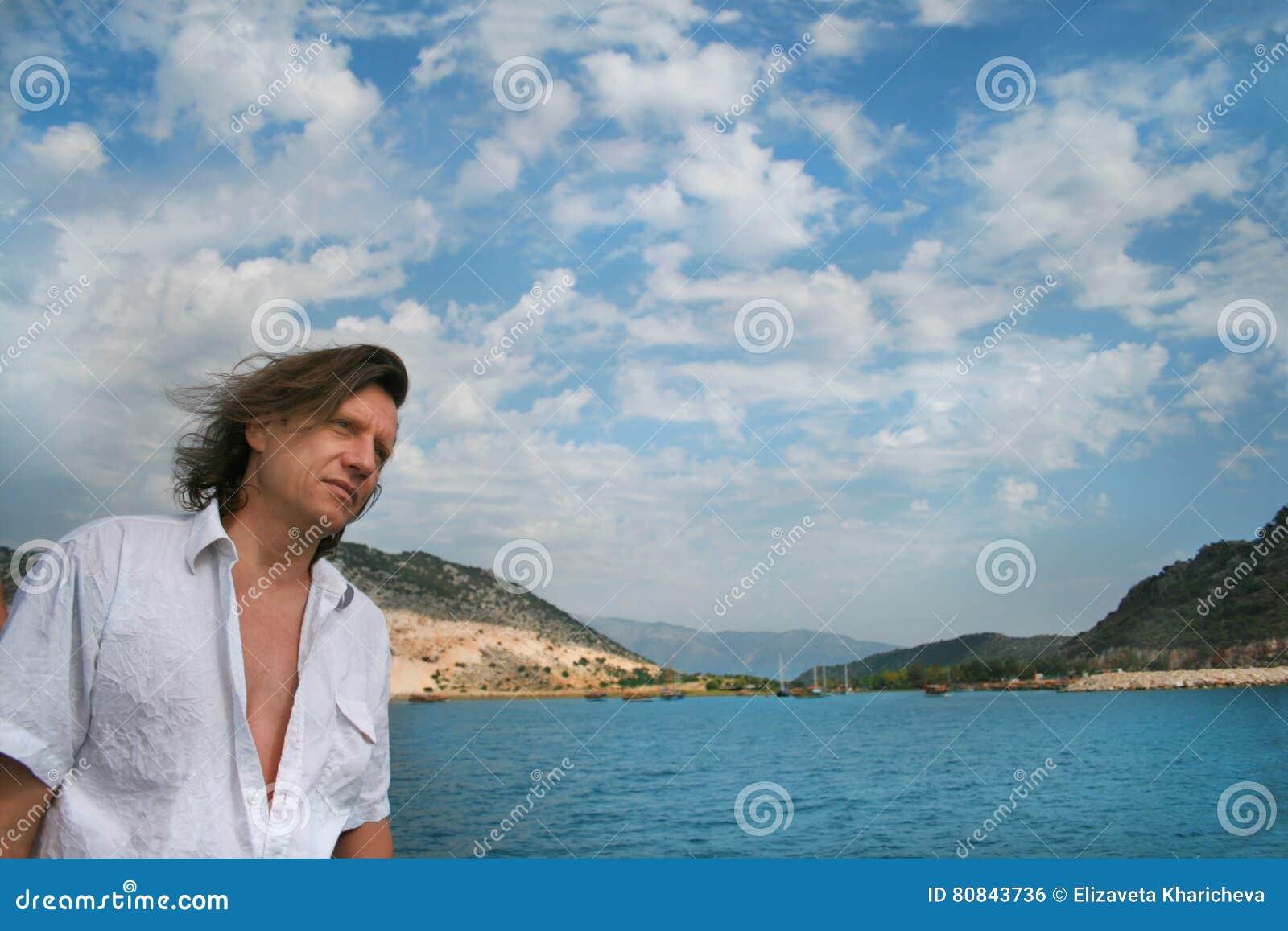 Ένα άτομο με μακρυμάλλη σε ένα υπόβαθρο της θάλασσας