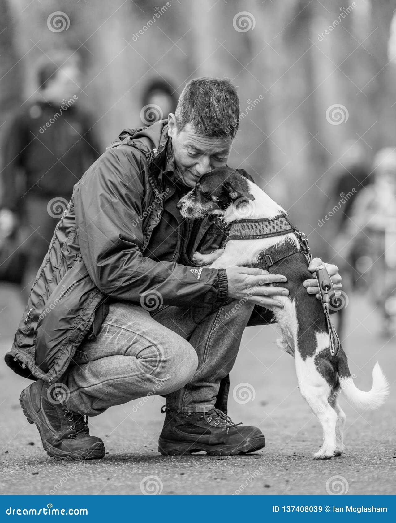 Ένα άτομο που αγκαλιάζει το σκυλί του στο πάρκο σε ένα σκυλί παρουσιάζει