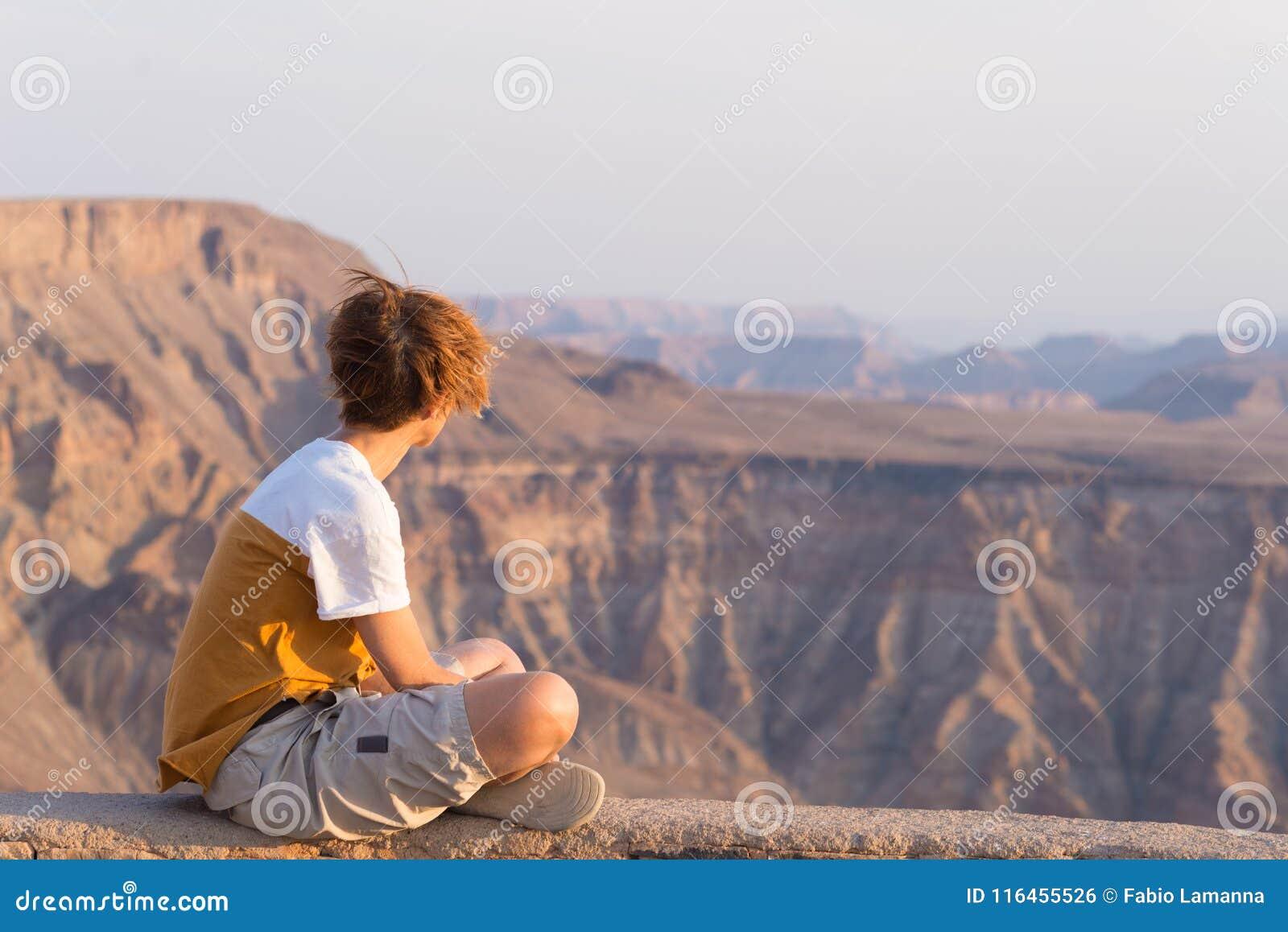 Ένα άτομο που εξετάζει το φαράγγι ποταμών ψαριών, φυσικός προορισμός ταξιδιού στη νότια Ναμίμπια Επεκτατική άποψη στο ηλιοβασίλεμ